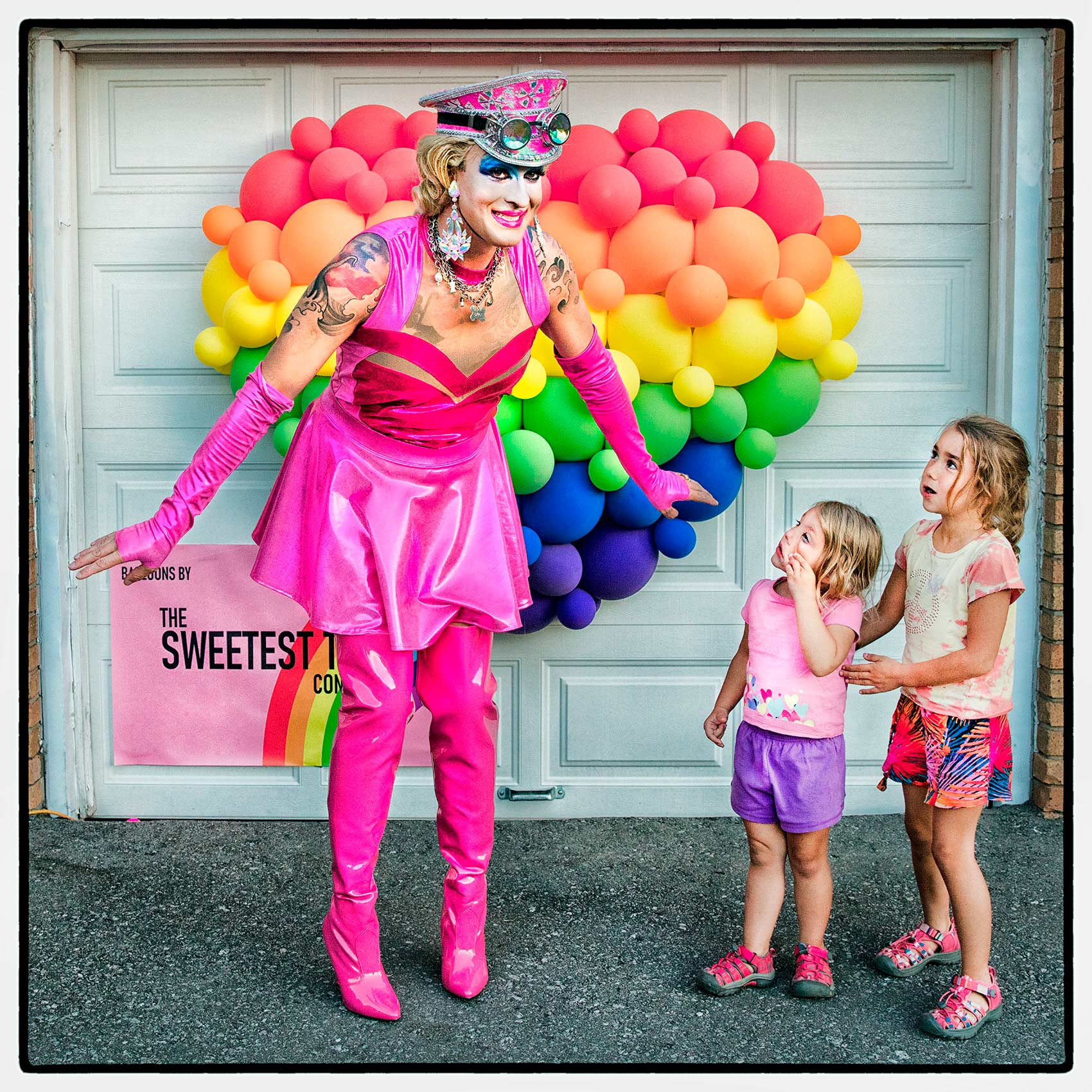 A drag queen looks surprised as she poses with suburban children after a toronto show