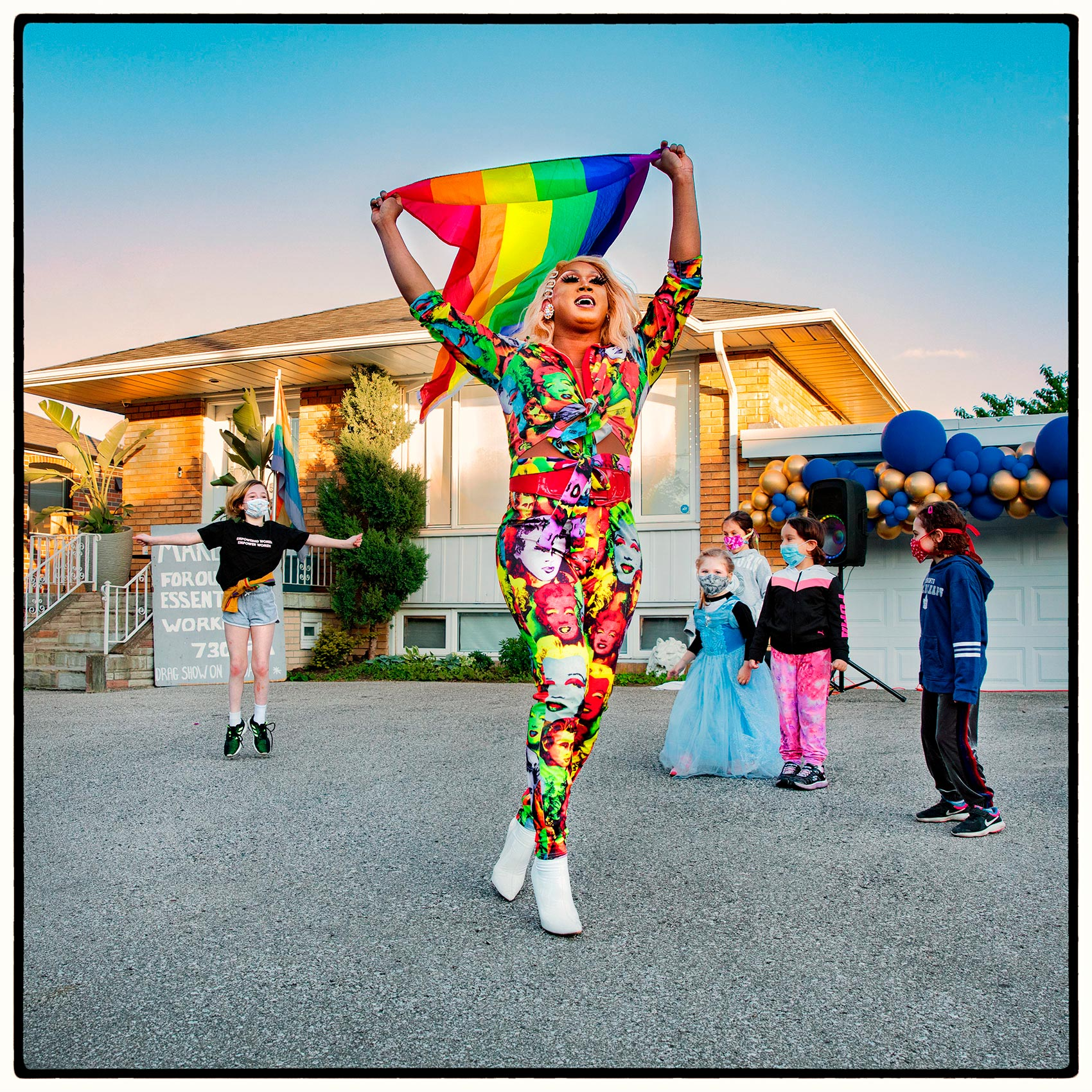 A drag queen holds up a pride flag during a suburban show in Toronto