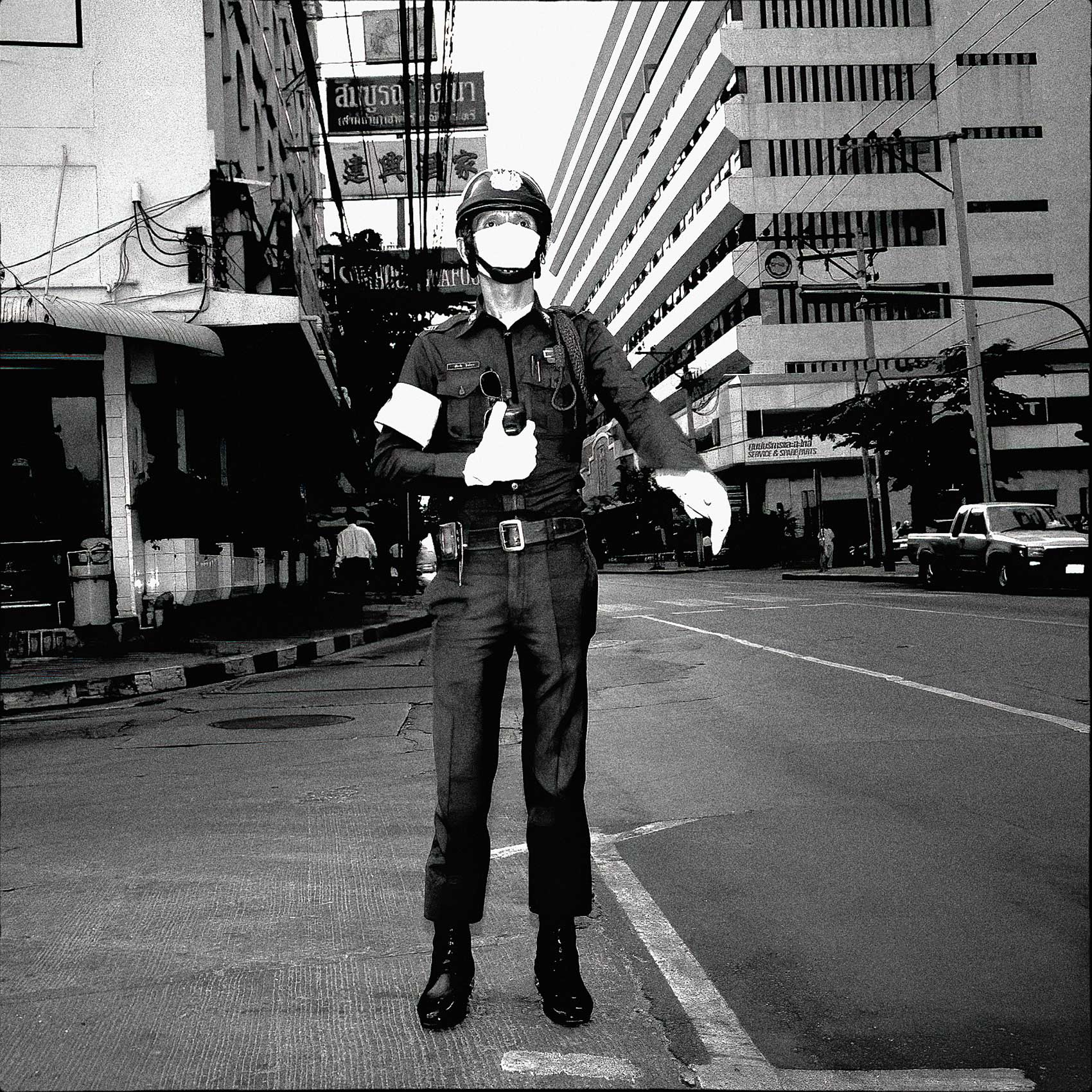 a-bangkok-policeman-wearing-a-face-mask-directs-traffic-in-the-downtown-core-of-the-city