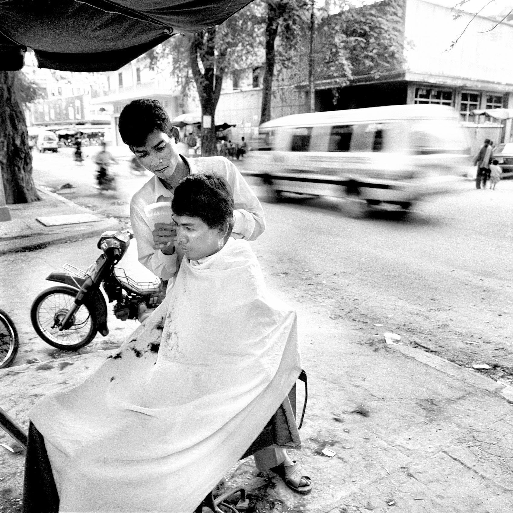 a-barber-in-angkor-wat-cuts-his-clients-hair-on-the-street