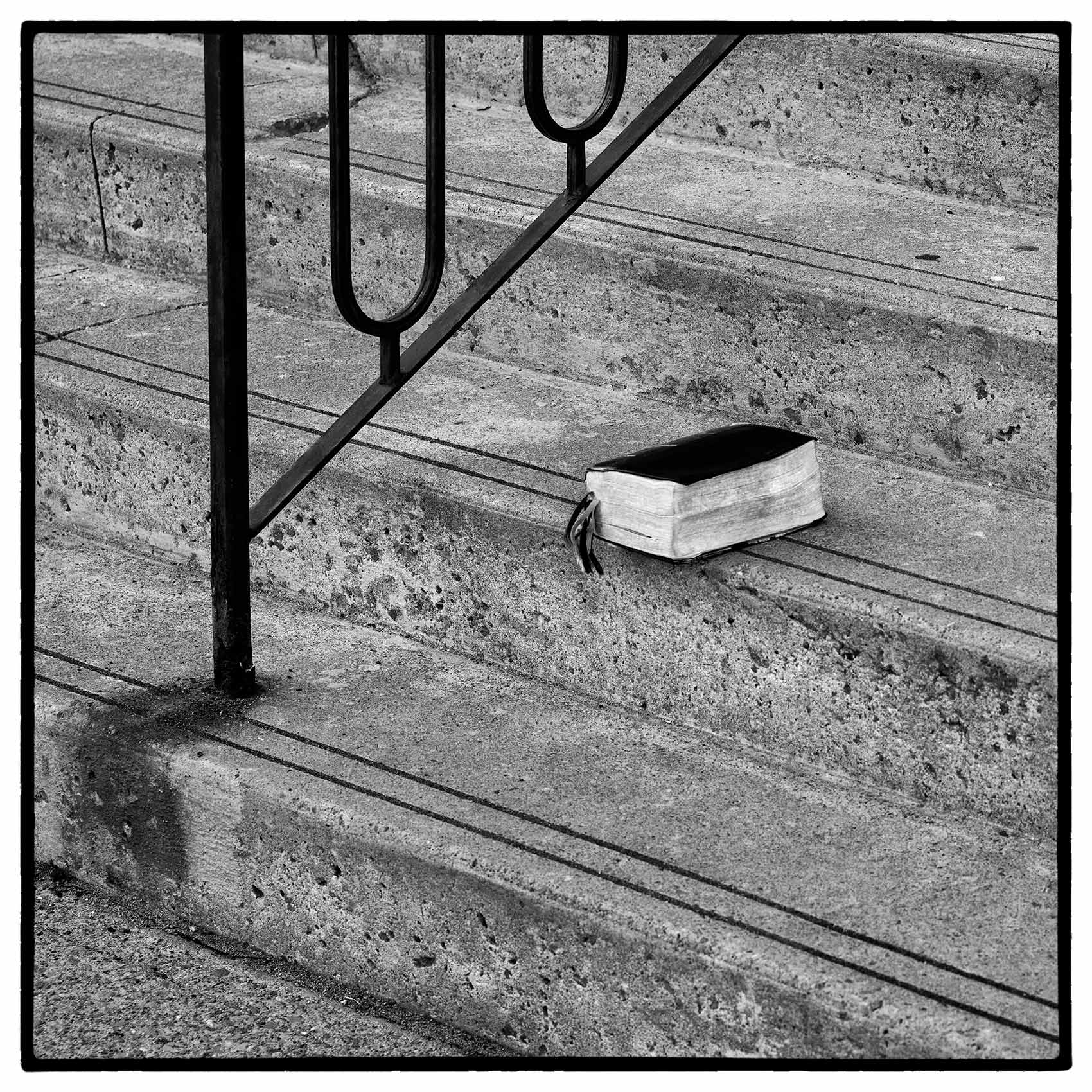 an old bible lays on the stairs of holy family church during the lockdown in toronto