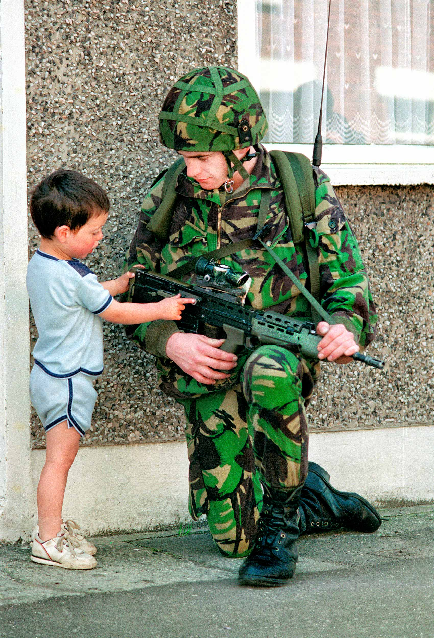a-british-soldier-shows-his-gun-to-a-boy-during-patrol-on-the-streets-of-catholic-west-belfast