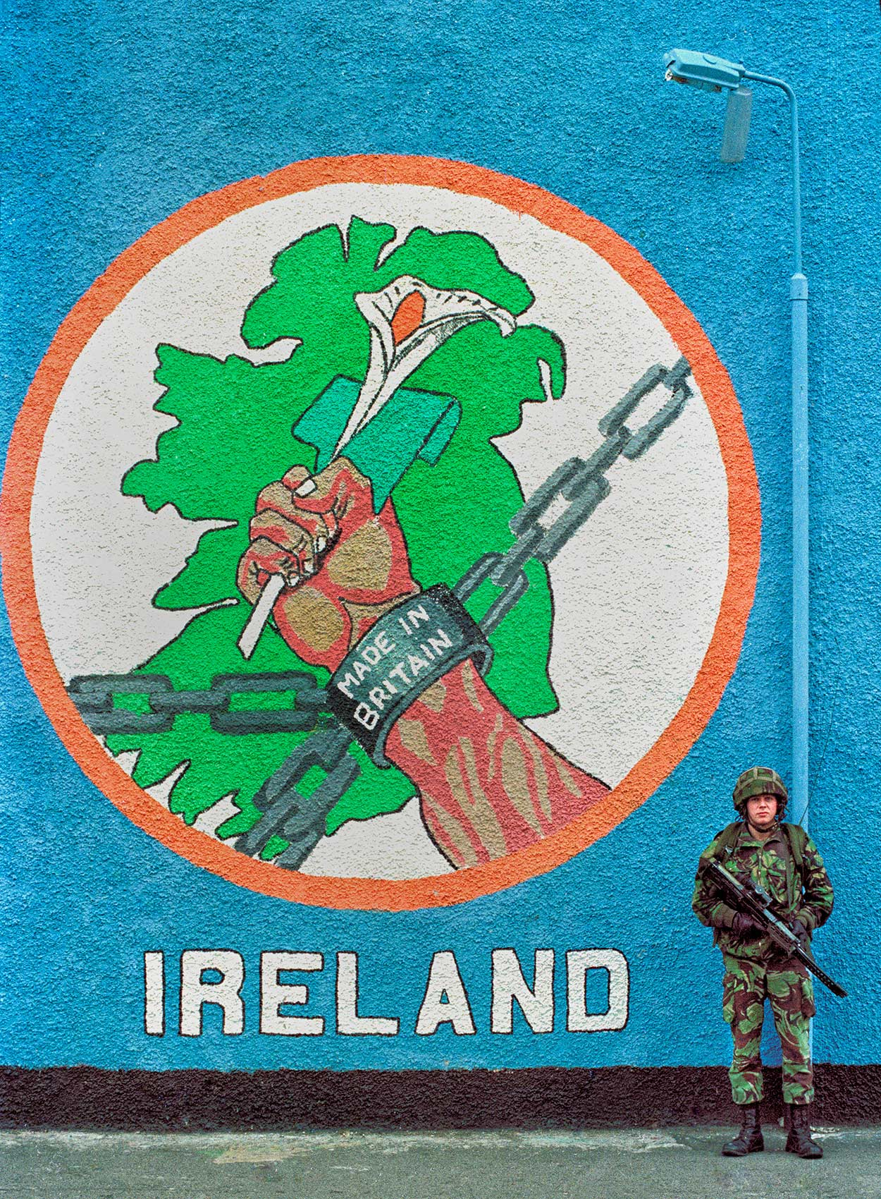 a-british-soldier-stands-guard-in-front-of-a-painted-mural-that-reads-made-in-britain-in-catholic-west-belfast