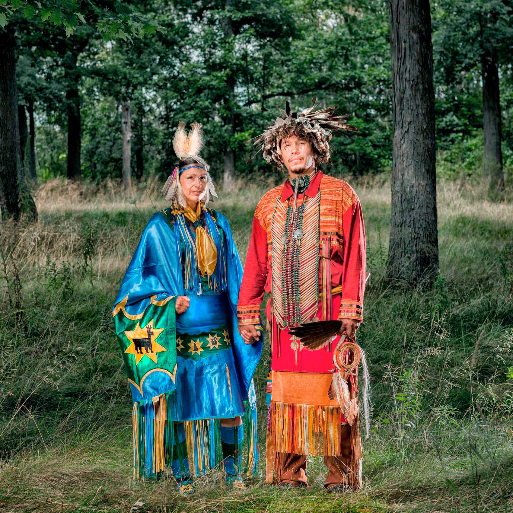 a-canadian-aboriginal-couple-stand-together-in-the-woods-wearing-ceremonial-clothing