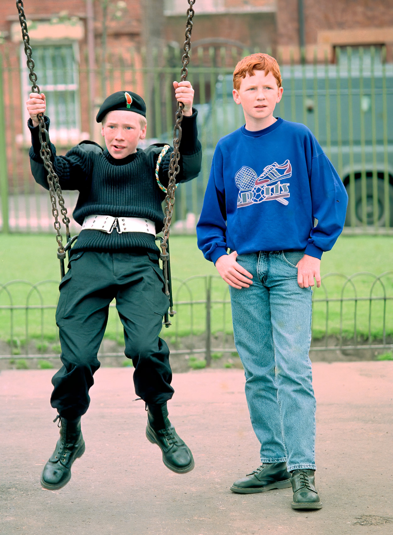 a-catholic-boy-swings-in-a-playground-in-catholic-west-belfast-as-his-friend-stands-by-his-side