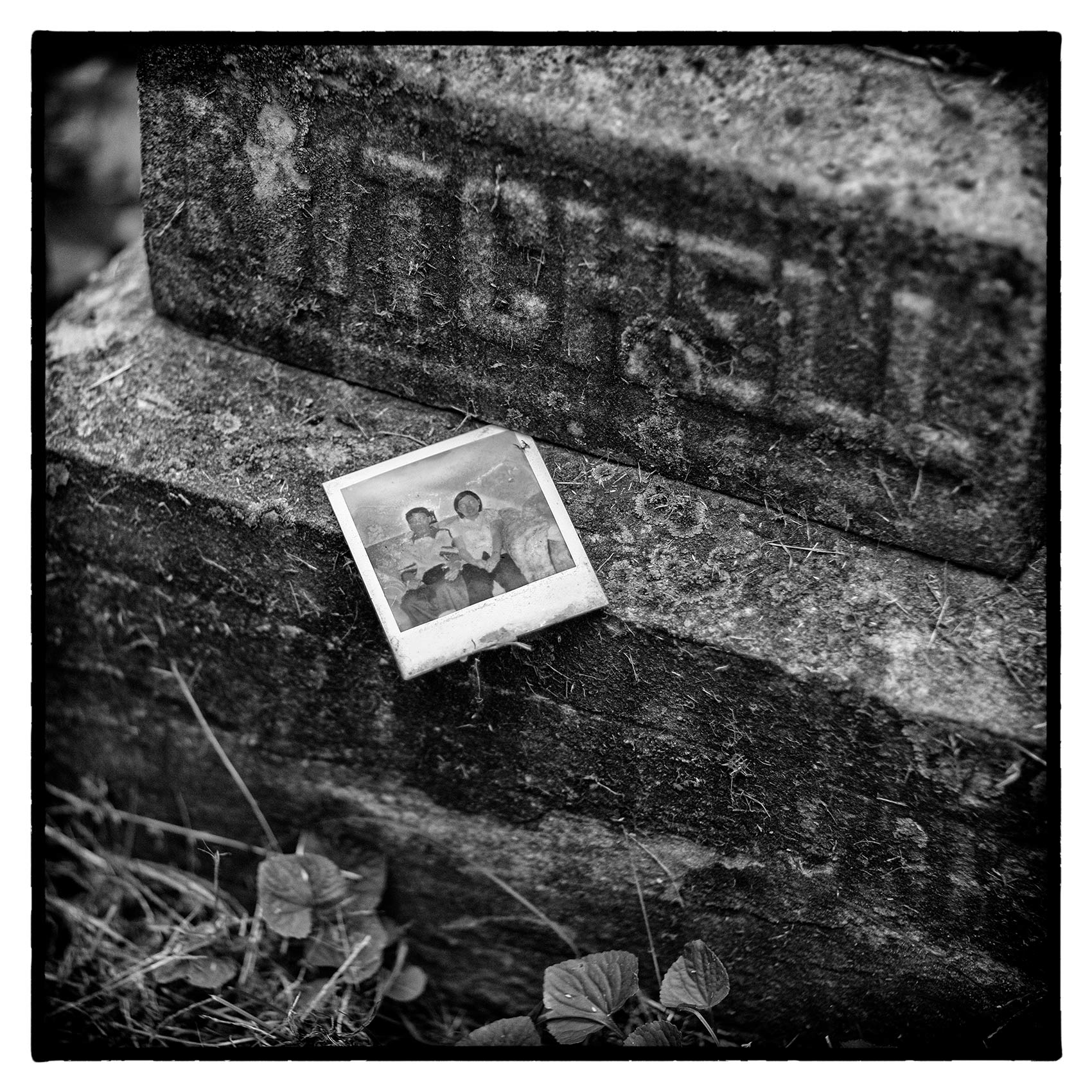an old polaroid is attached to a stone grave at Torontos St. James Cemetary