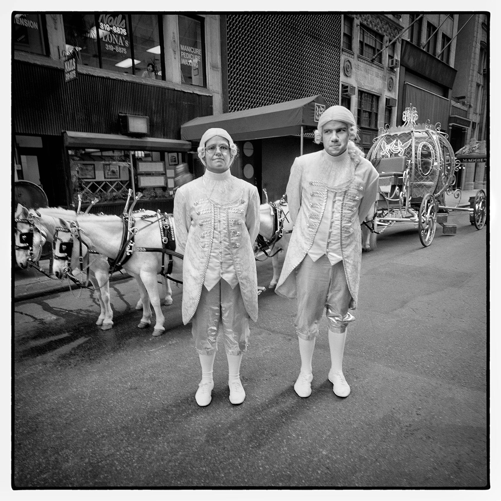 a-couple-dressed-as-carriage-drivers-pose-outside-the-cinderalla-carriage-before-it-appears-in-the-new-york-thanksgiving-parade-in-manhattan