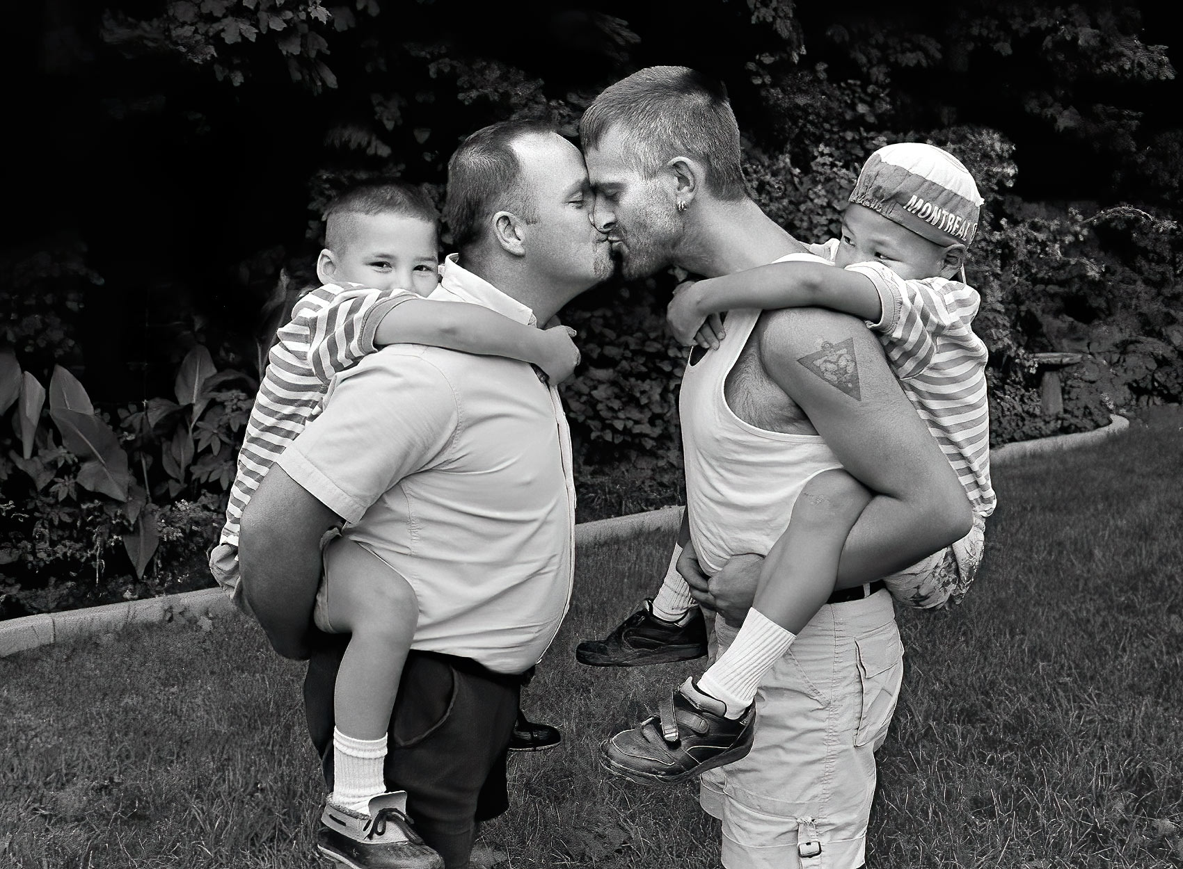a-gay-male-couple-kiss-in-their-back-garden-while-piggy-backing-both-of-their-adopted-sons