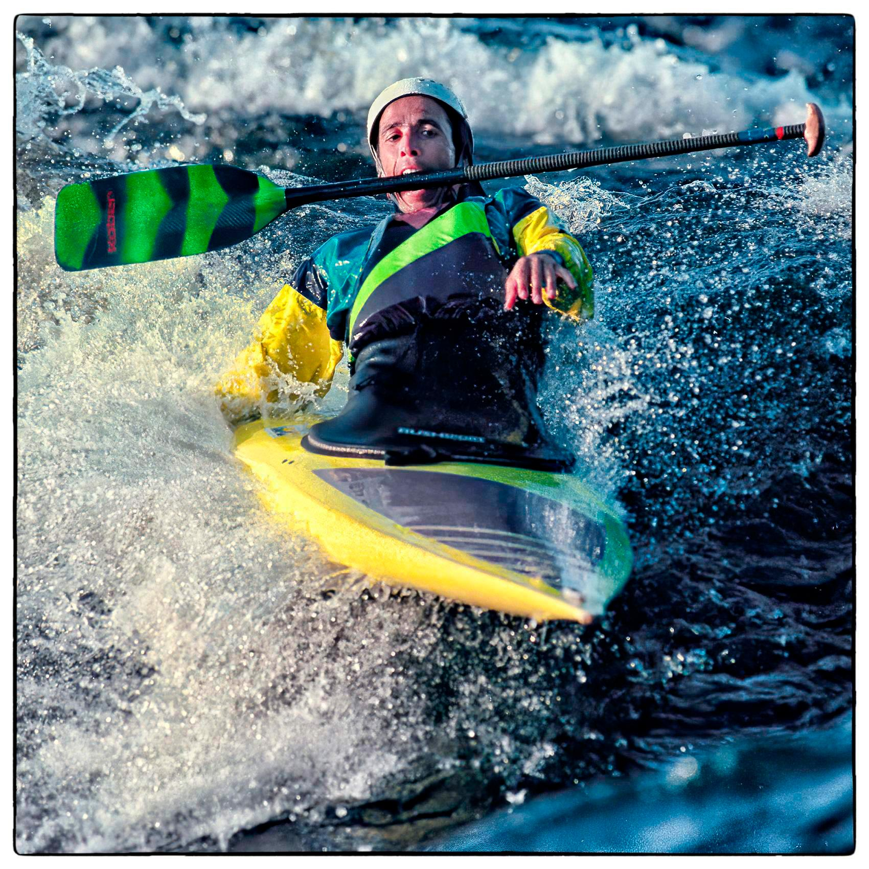 a-man-grimaces-as-he-kayaks-and-holds-his-paddle-in-his-mouth-as-he-surfs-the-waves-on-the-ottawa-river