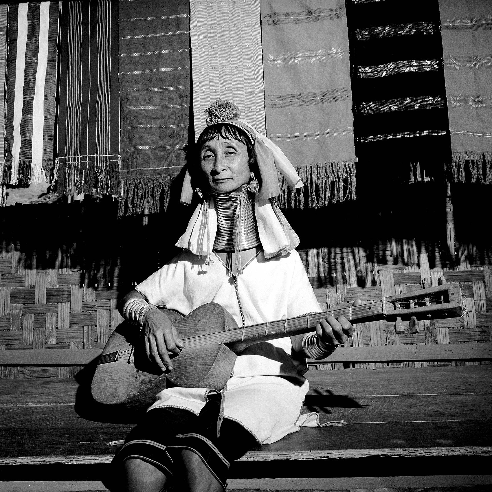 a-woman-from-the-red-karen-tribe-in-burma-plays-the-guitar-in-her-village-in-thailand