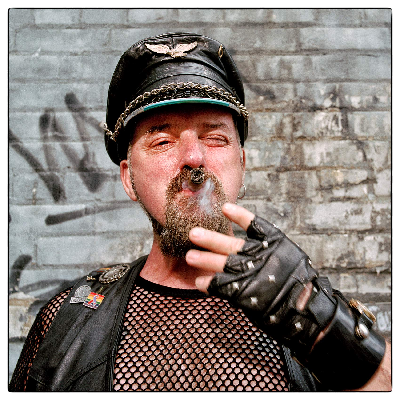 a-leather-daddy-smokes-a-large-cigar-while-posing-for-a-photo-at-toronto-gay-pride