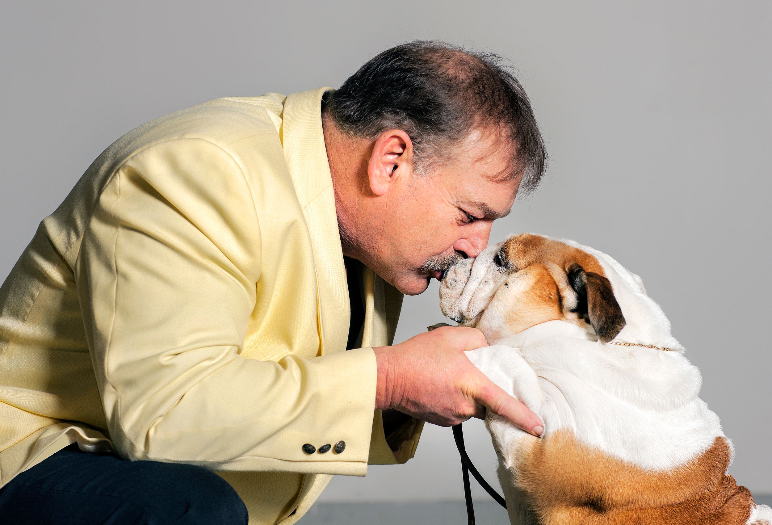 a-man-at-a-dog-show-kisses-his-pet-bulldog-after-he-pulls-off-a-winning-performance