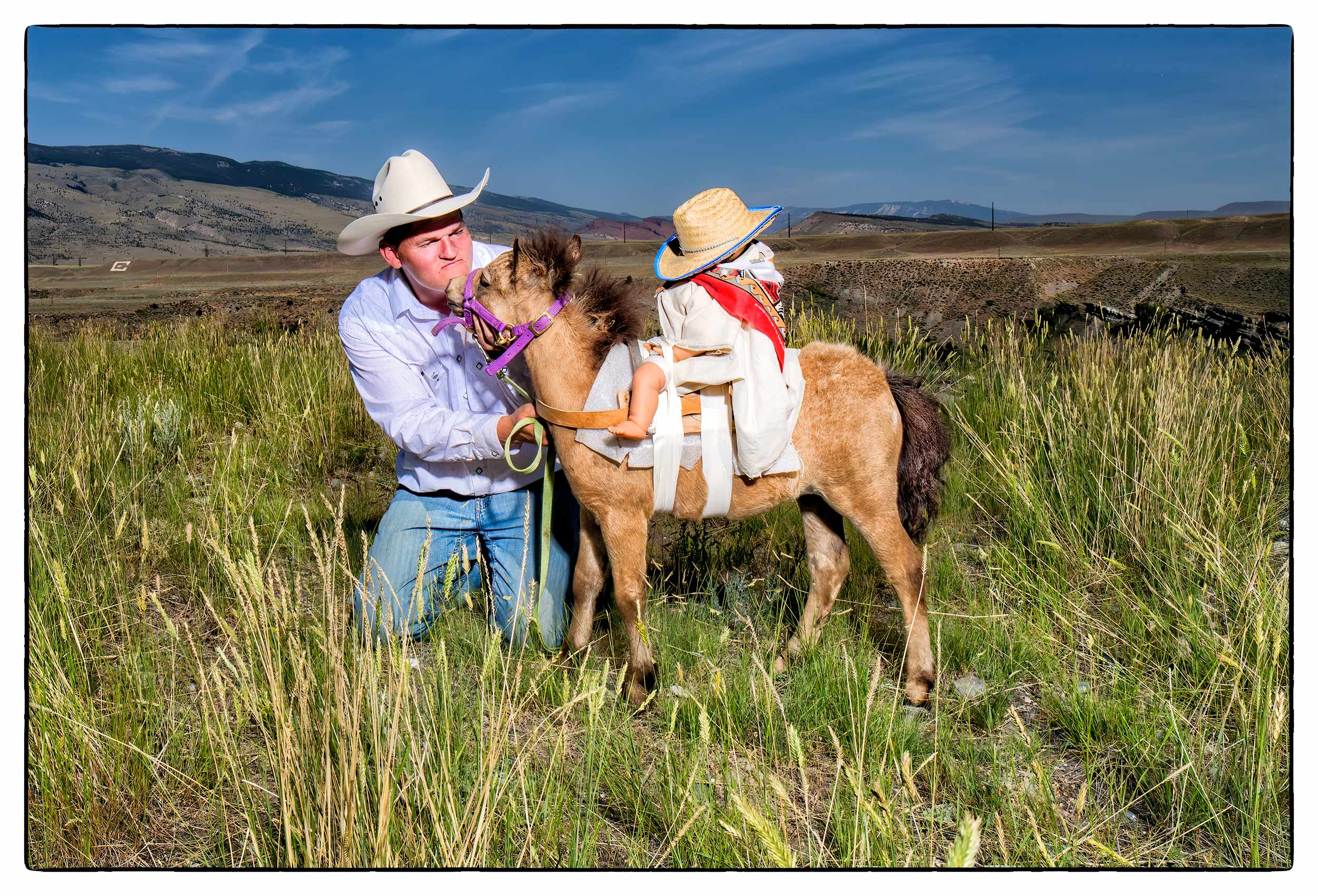 a-man-gets-kissed-by-a-miniature-donkey-in-a-field-in-cody-wyoming-usa