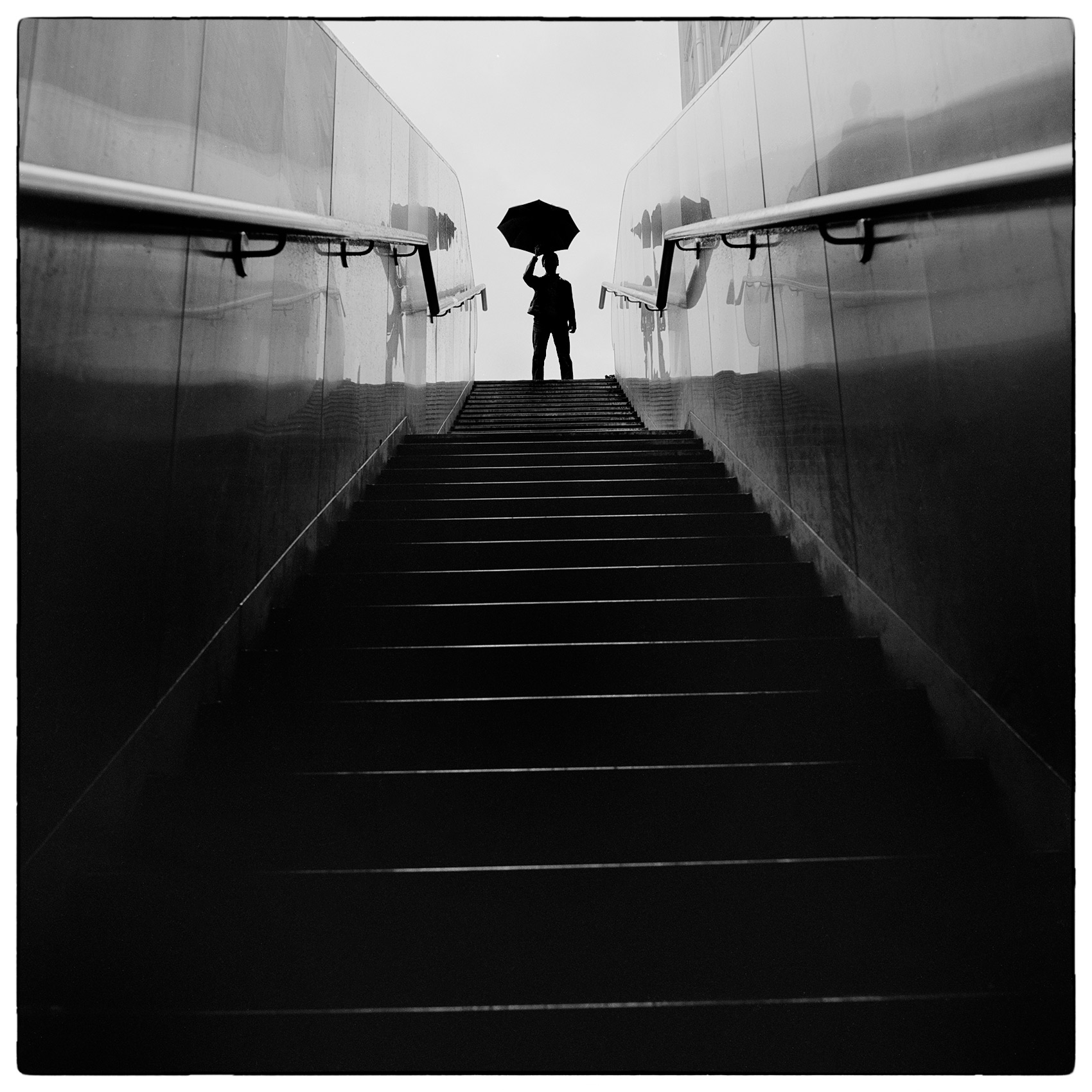 a-man-holding-an-umbrella-is-silhouetted-as-gets-ready-to-ascend-a-staircase-in-paris-france
