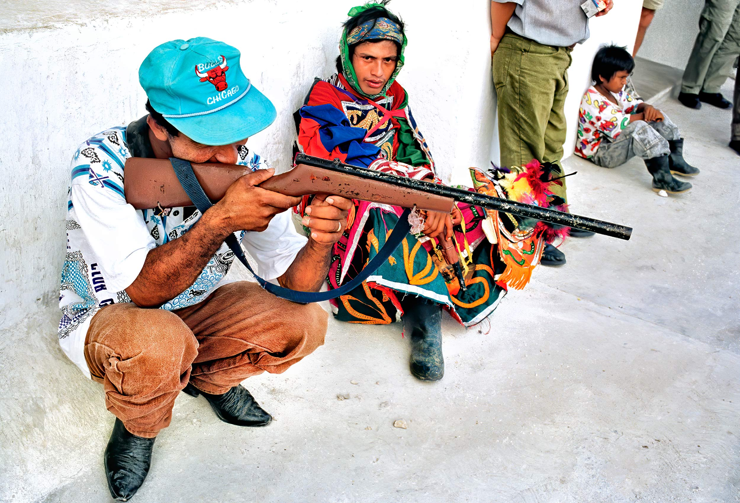 a-man-holds-a-fake-rifle-used-in-a-mayan-festival-in-flores-guatemala
