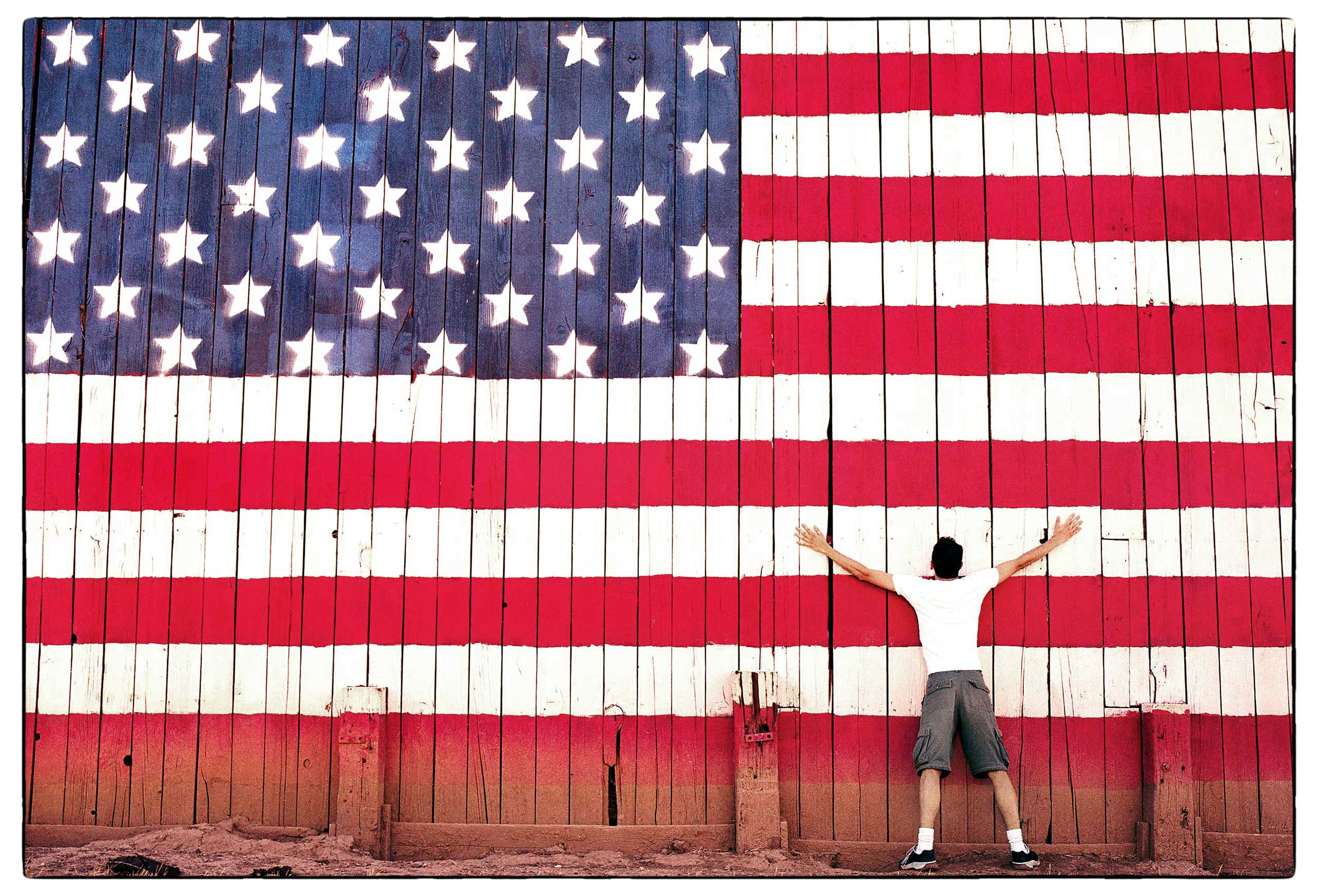 a-man-hugs-the-american-flag-on-the-side-of-a-barn-in-san-mateo-california