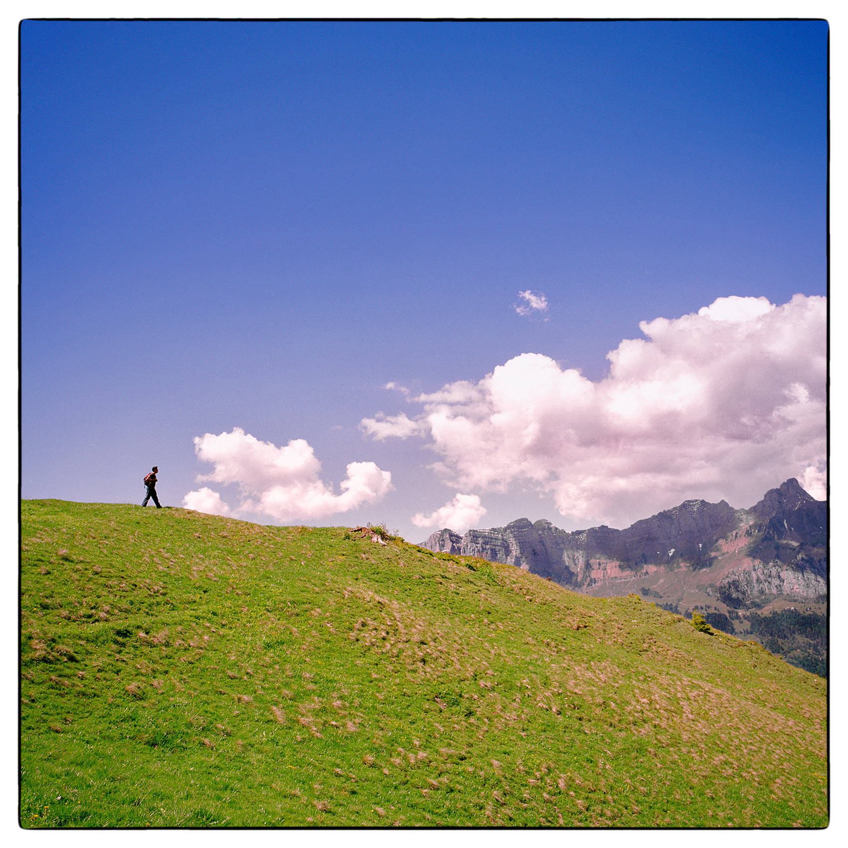 a-man-is-dwarfed-by-the-swiss-alps-as-he-hikes-on-a-neaby-hillside-outside-of-zurich-switzerland