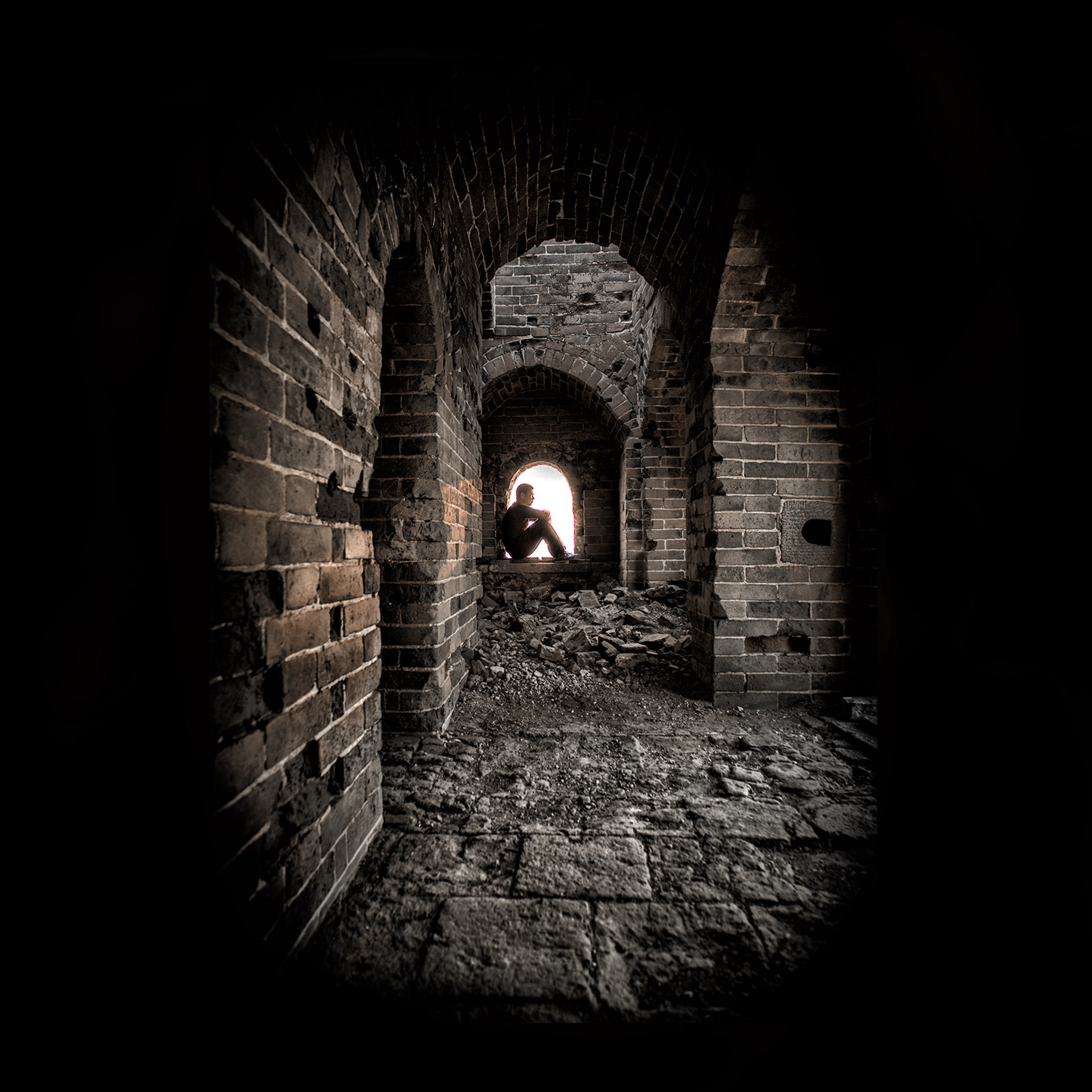 a-man-is-silhouetted-as-he-sits-inside-a-windowsill-in-an-ancient-guard-tower-on-the-great-wall-of-china