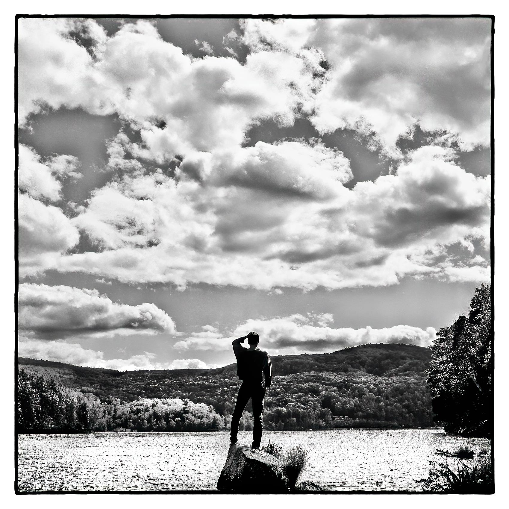 a-man-is-silhouetted-by-the-sun-as-he-stands-on-a-rock-on-meech-lake-in-gatineau-quebec-canada