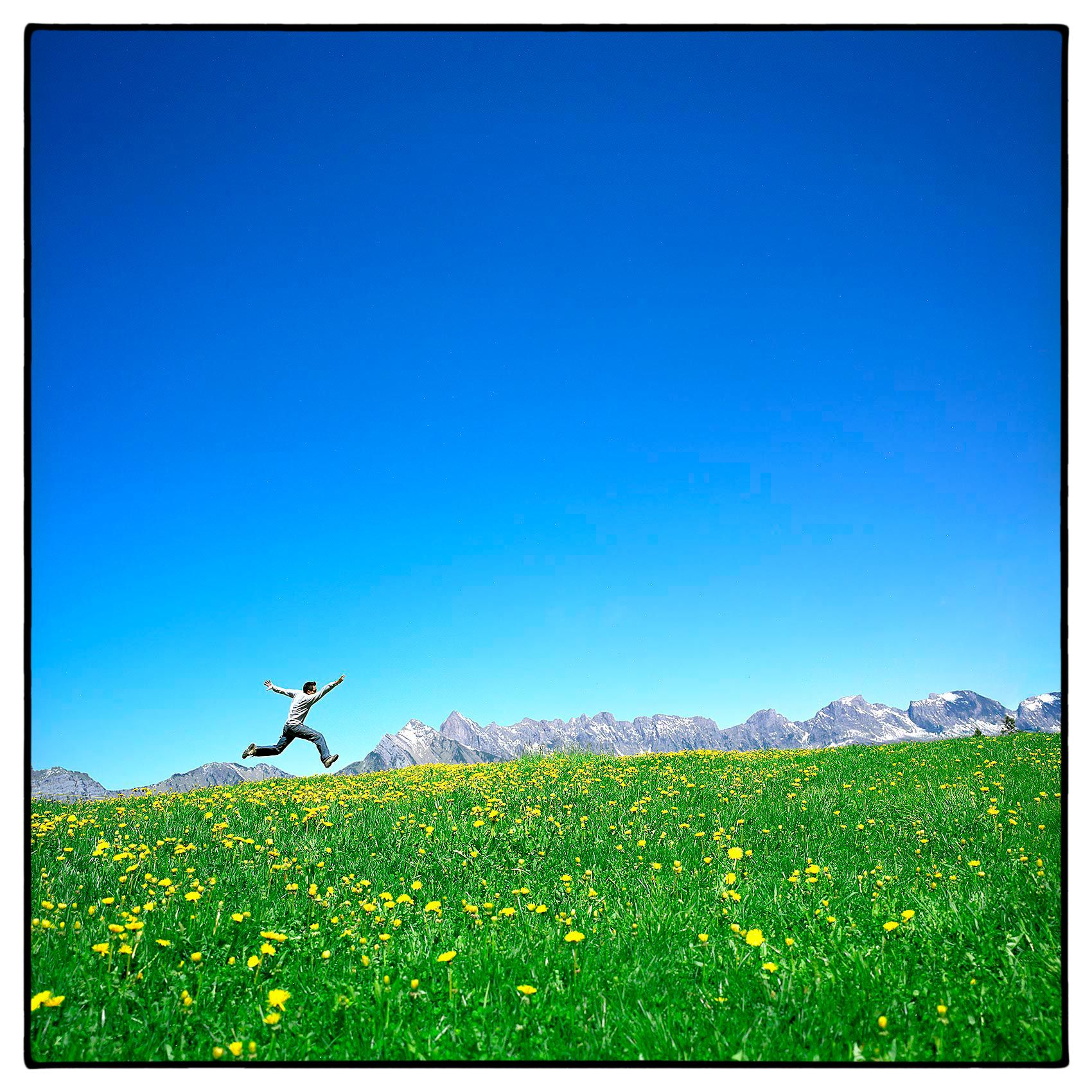 viradeth-manixab-jumps-in-a-green-field-in-front-of-the-swiss-alps