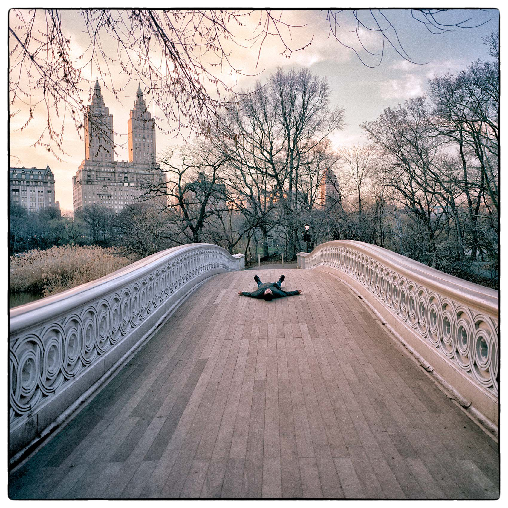 a-man-lays-in-the-middle-of-a-bridge-in-new-yorks-central-park-creating-an-artistic-photo-in-the-late-afternoon