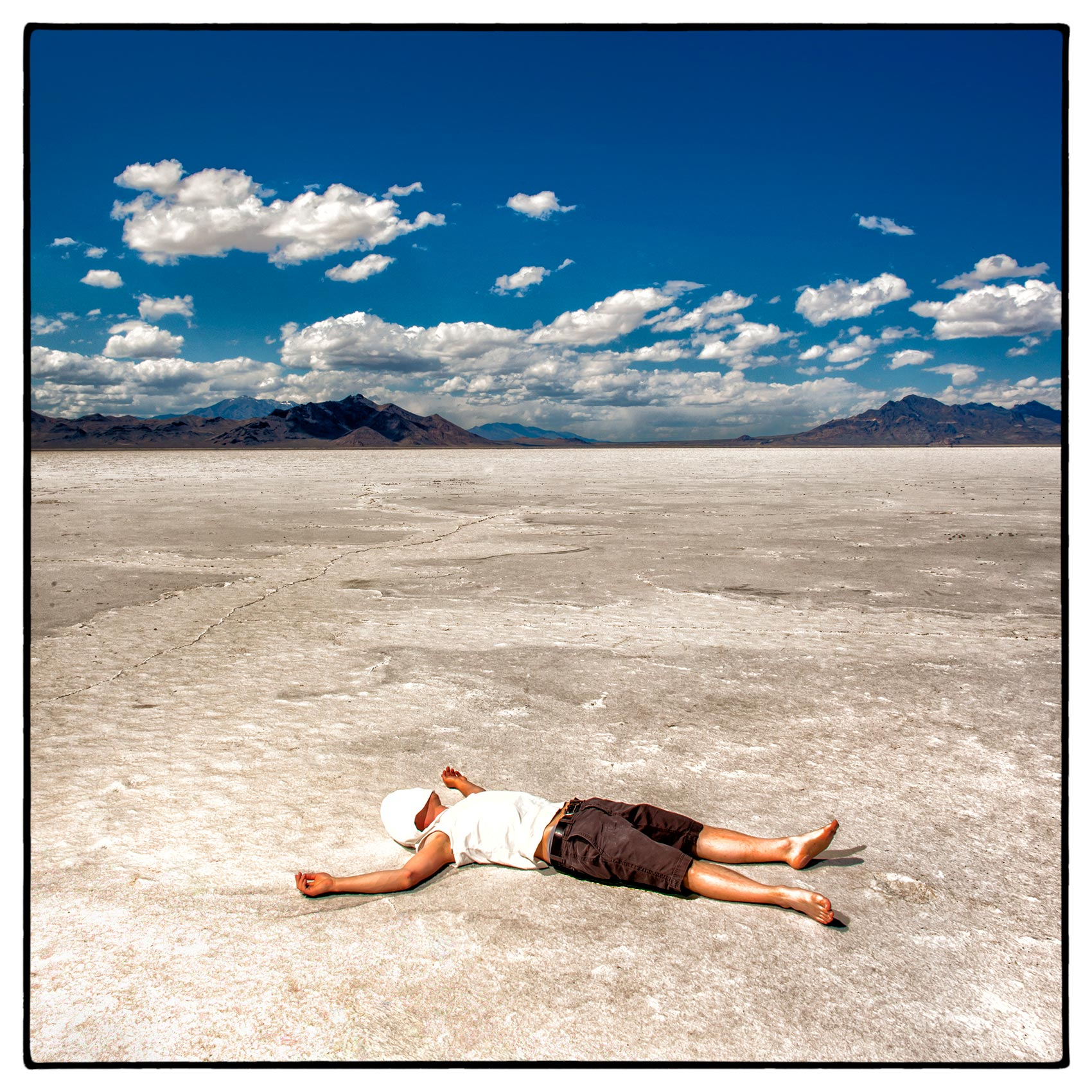 a-man-lays-on-the-bed-of-the-bonneville-salt-flats-outside-of-salt-lake-city-utah