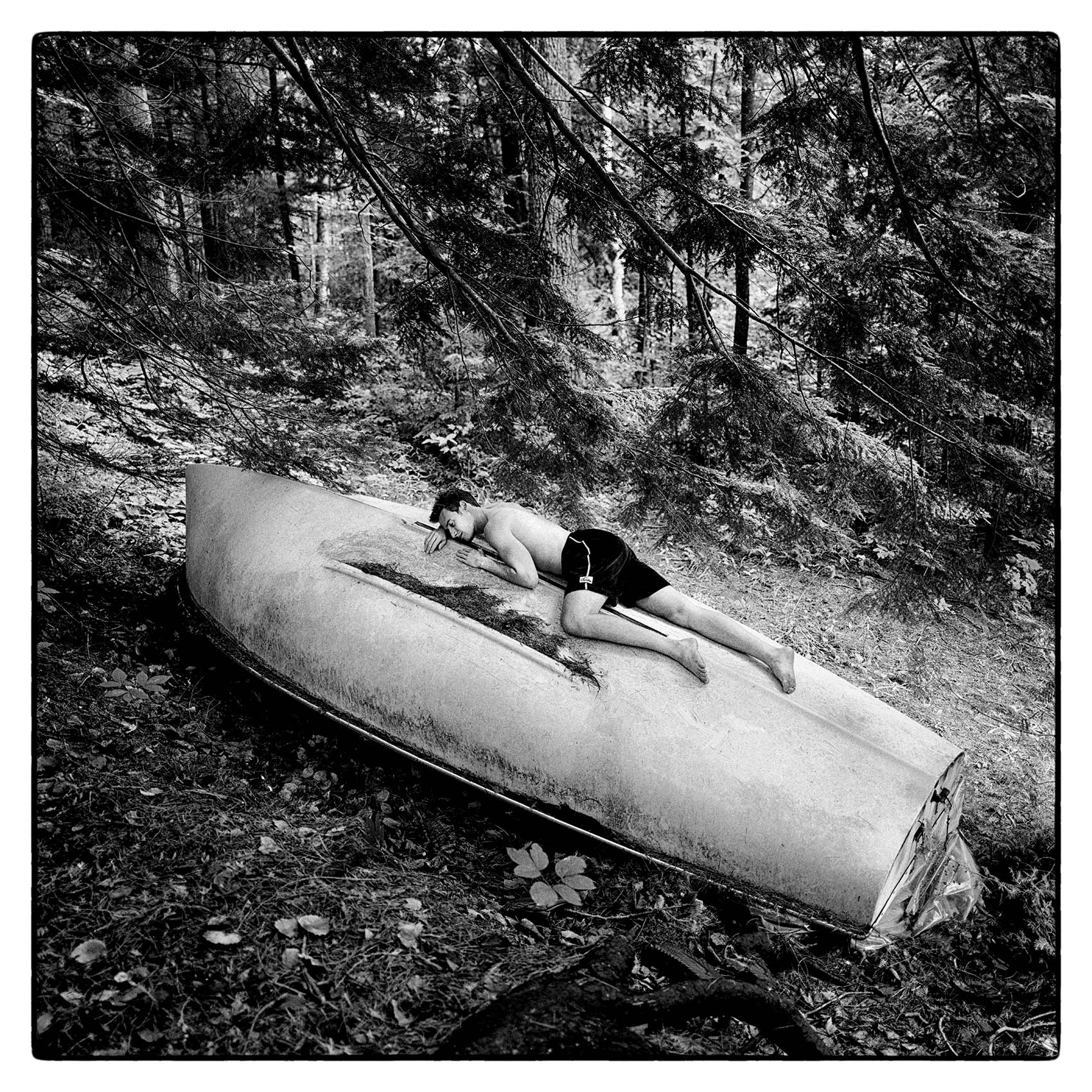 a-man-lays-on-top-of-an-overturned-sailboat-in-the-sun-at-his-cottage-in-northern-ontario