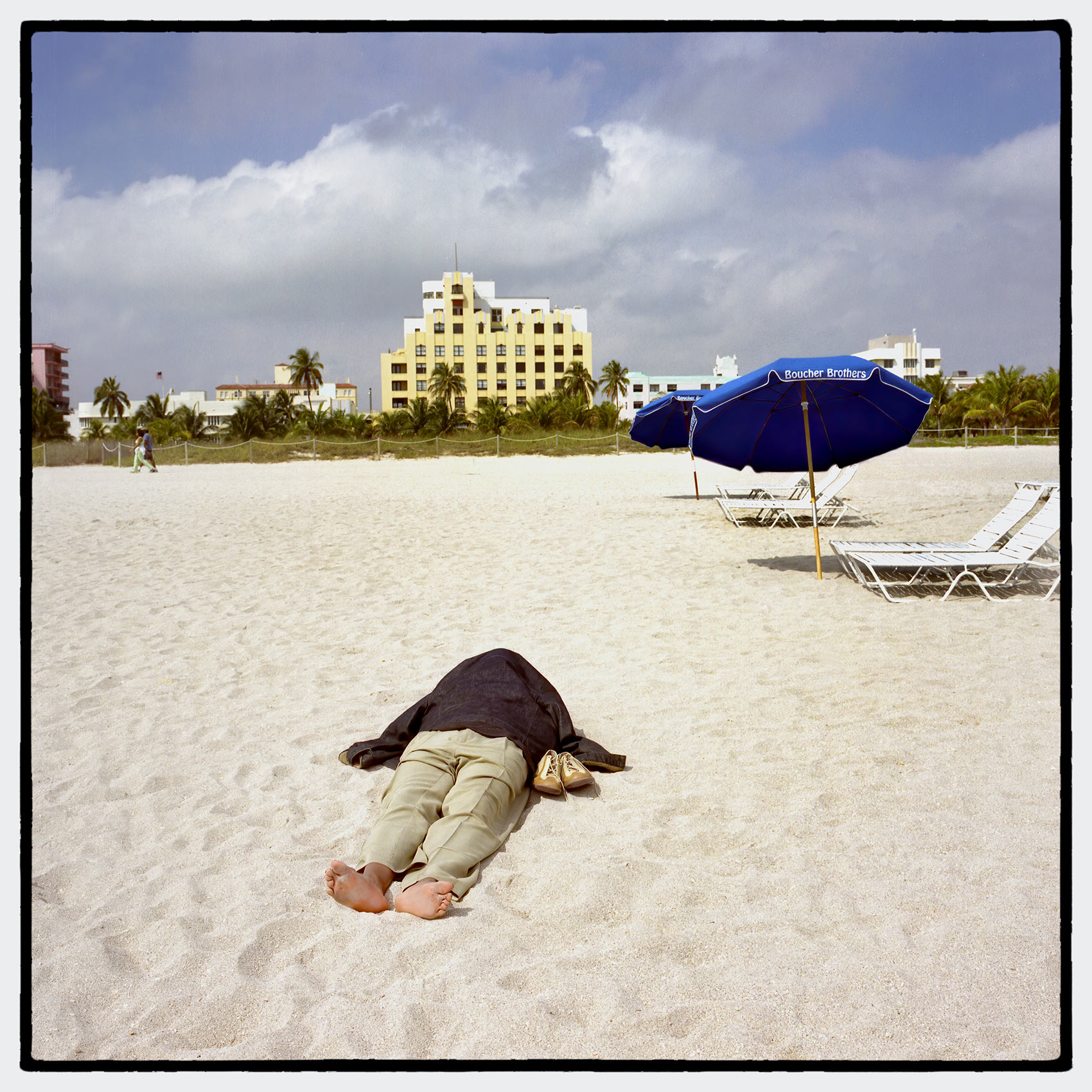 a-man-looks-dead-as-he-lays-sleeping-on-miami-beach-covered-in-a-jacket