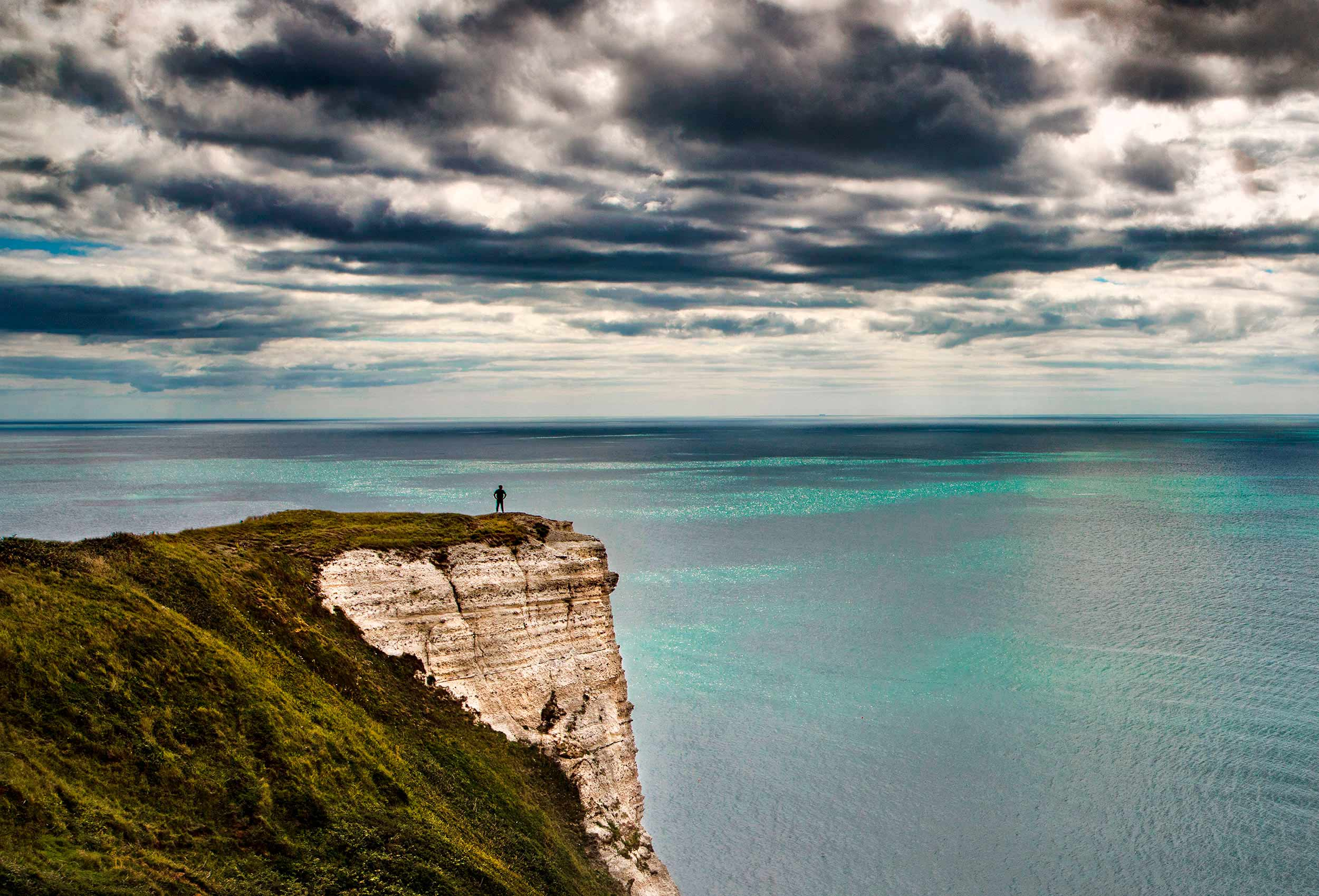 A man on a cliff on the Jurassic Coast in Devonshire by Top Travel Photographer John Hryniuk