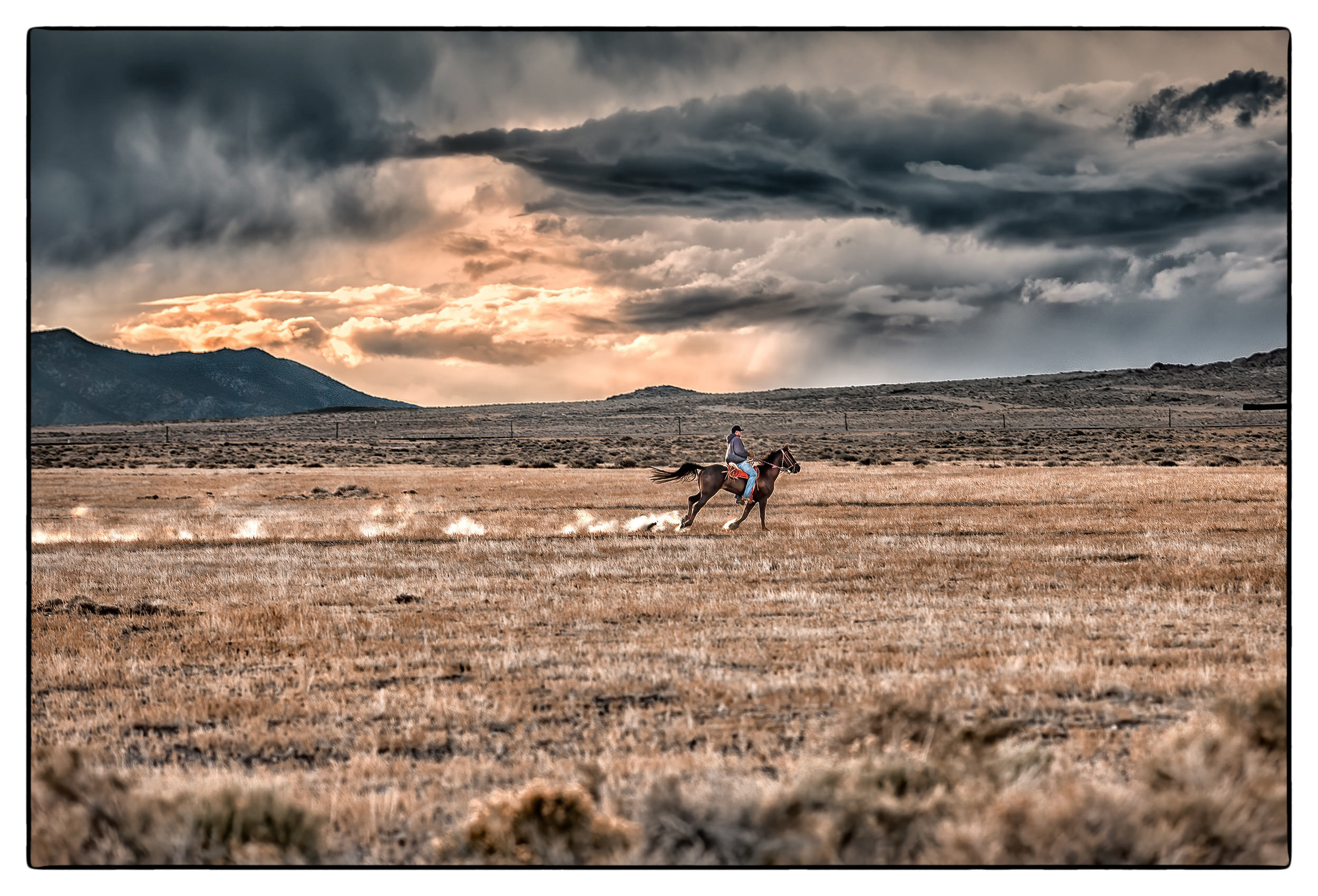 a-man-on-a-horseback-rush-back-to-their-farm-to-beat-an-approaching-storm-in-the-nevada-desert