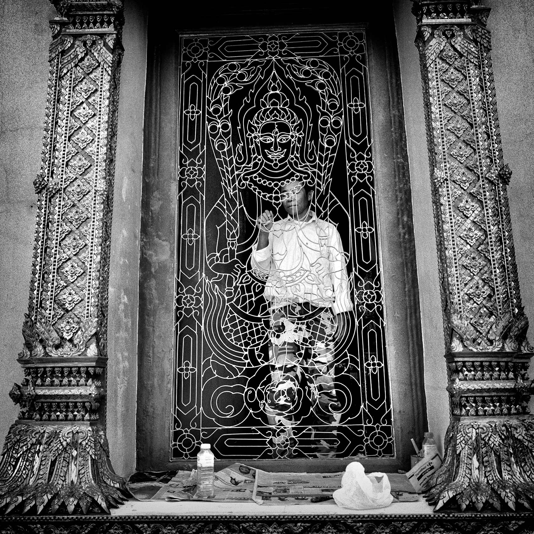 a-man-pauses-as-he-paints-an-gold-iron-gate-at-a-buddhist-temple-in-bangkok-thailand