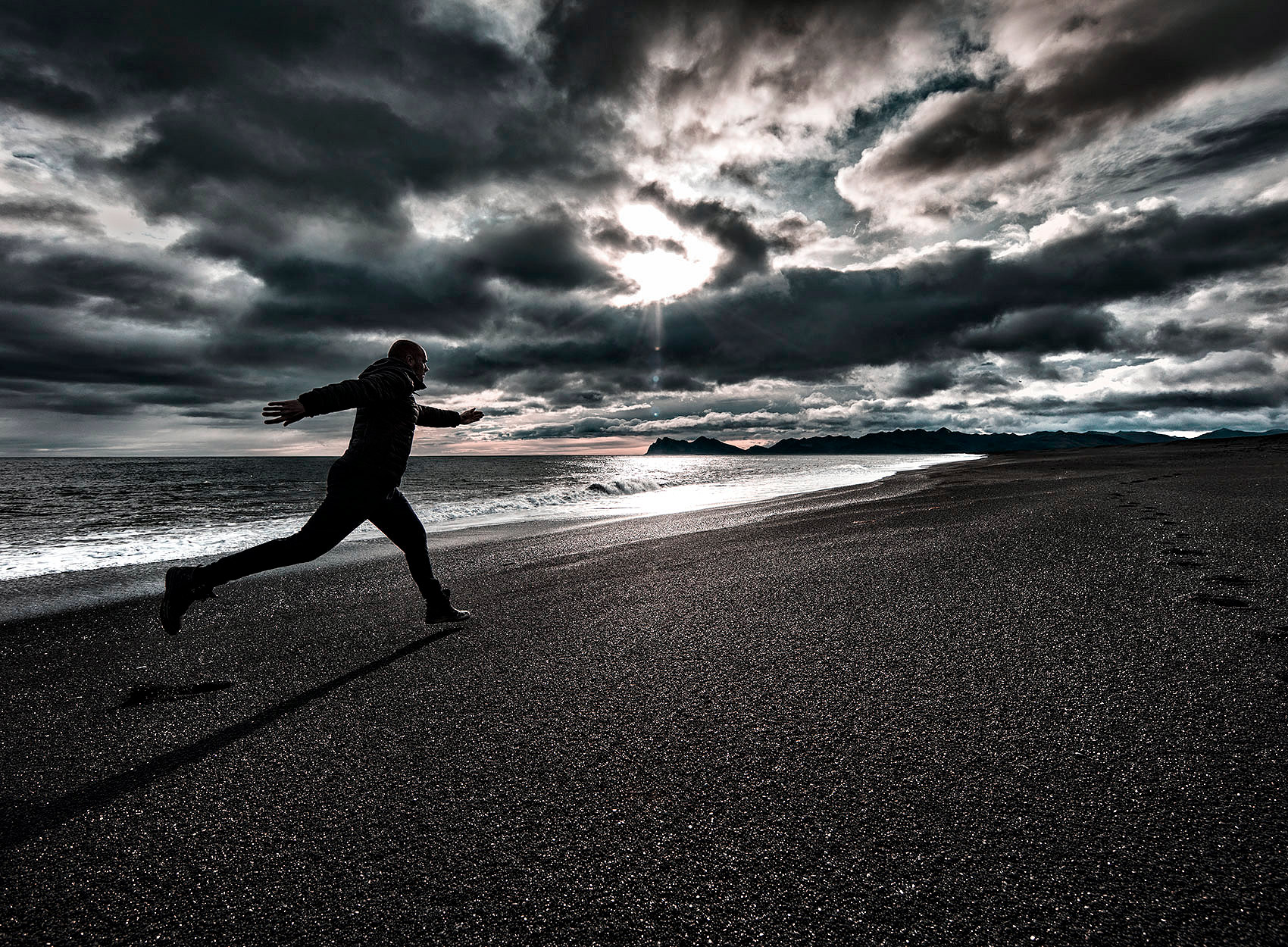 a man runs on an icelandic volcanic beach during an early fall sunset