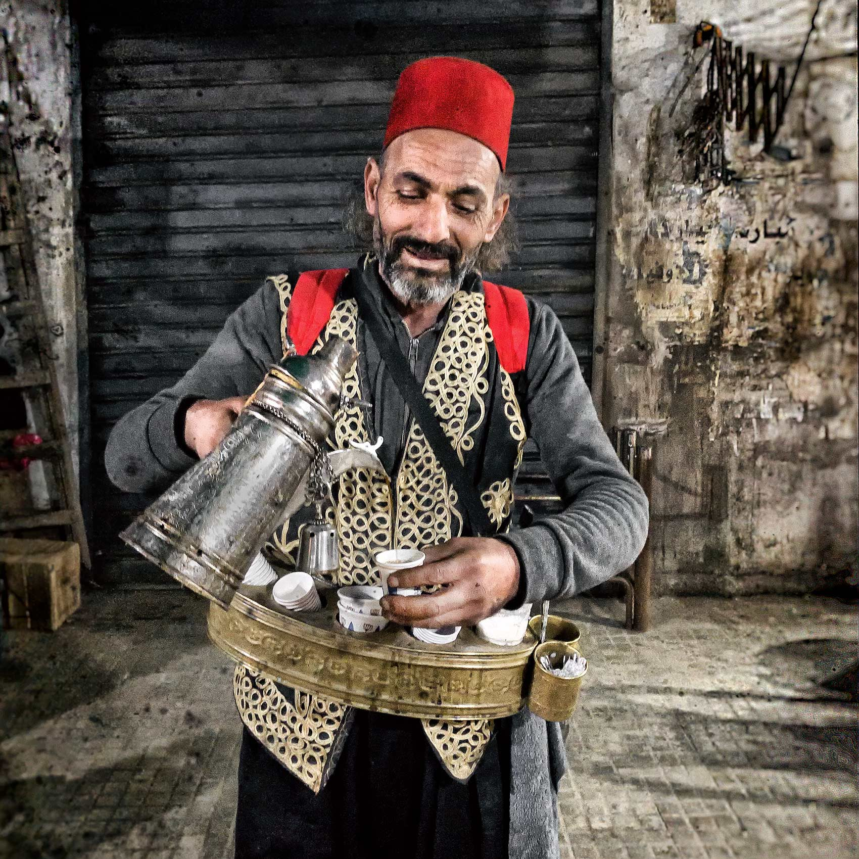 a man sells tea to street vendors in mar elias market in south beirut