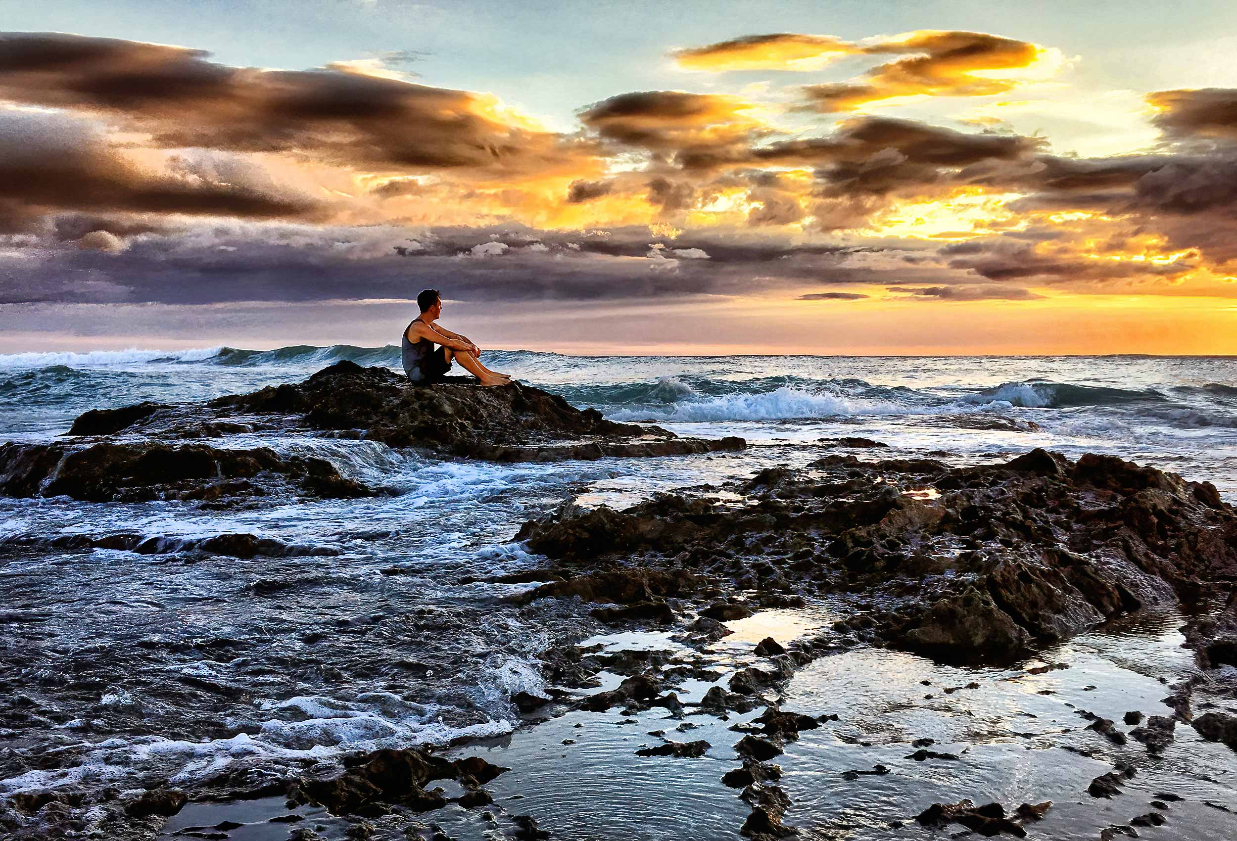 a-man-sits-on-a-rock-watching-a-sunset-by-an-editorial-photographer