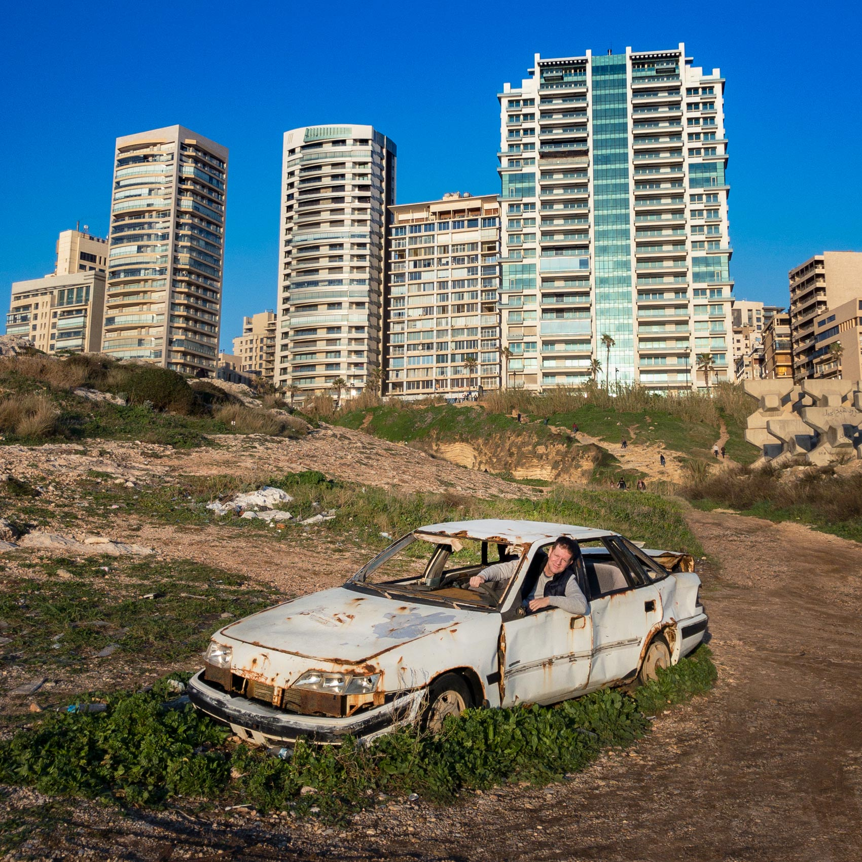 a man sits inside a wrecked car on the hillside in central beirut
