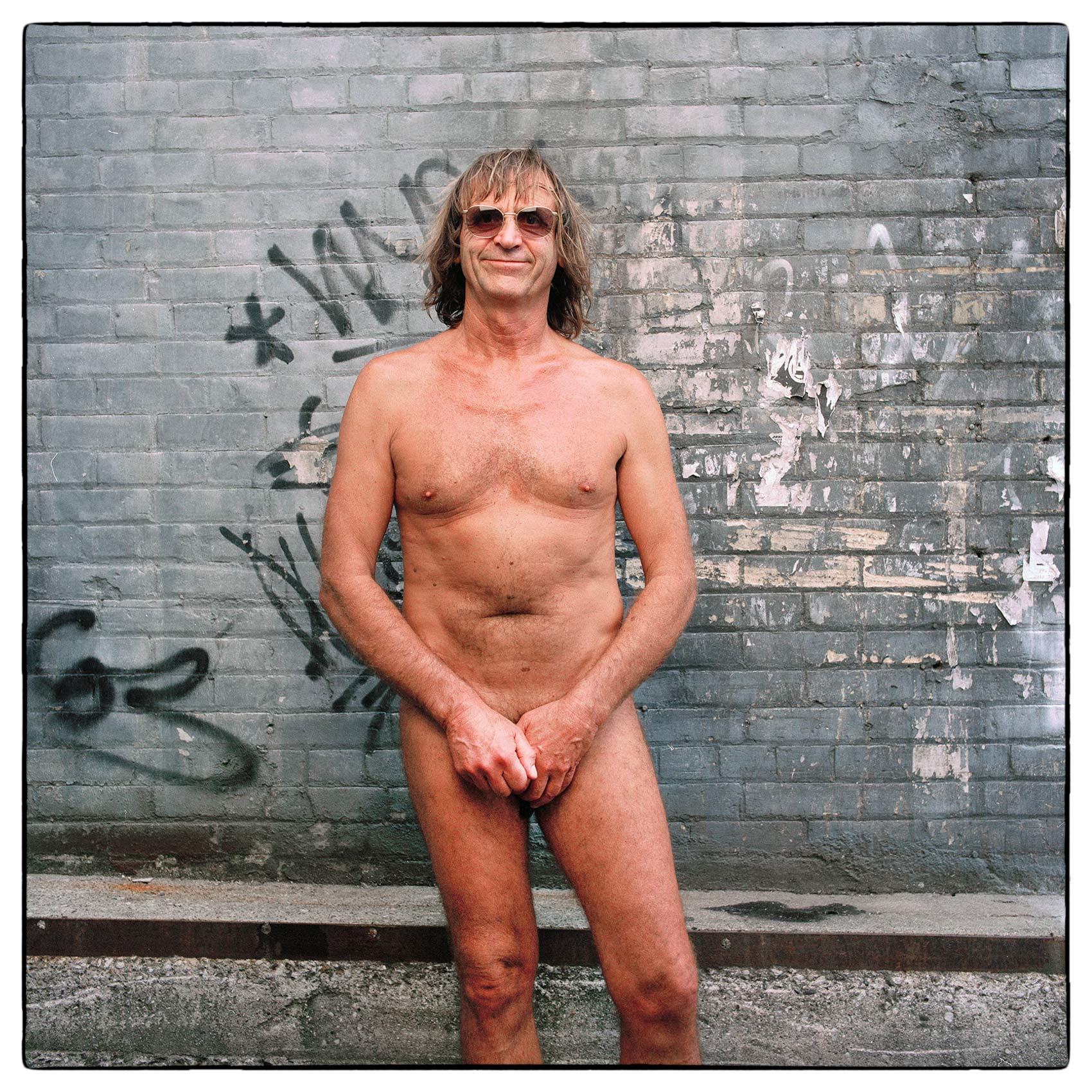 a-man-stands-naked-covering-his-genitals-for-a-photography-portrait-at-the-toronto-gay-pride-parade