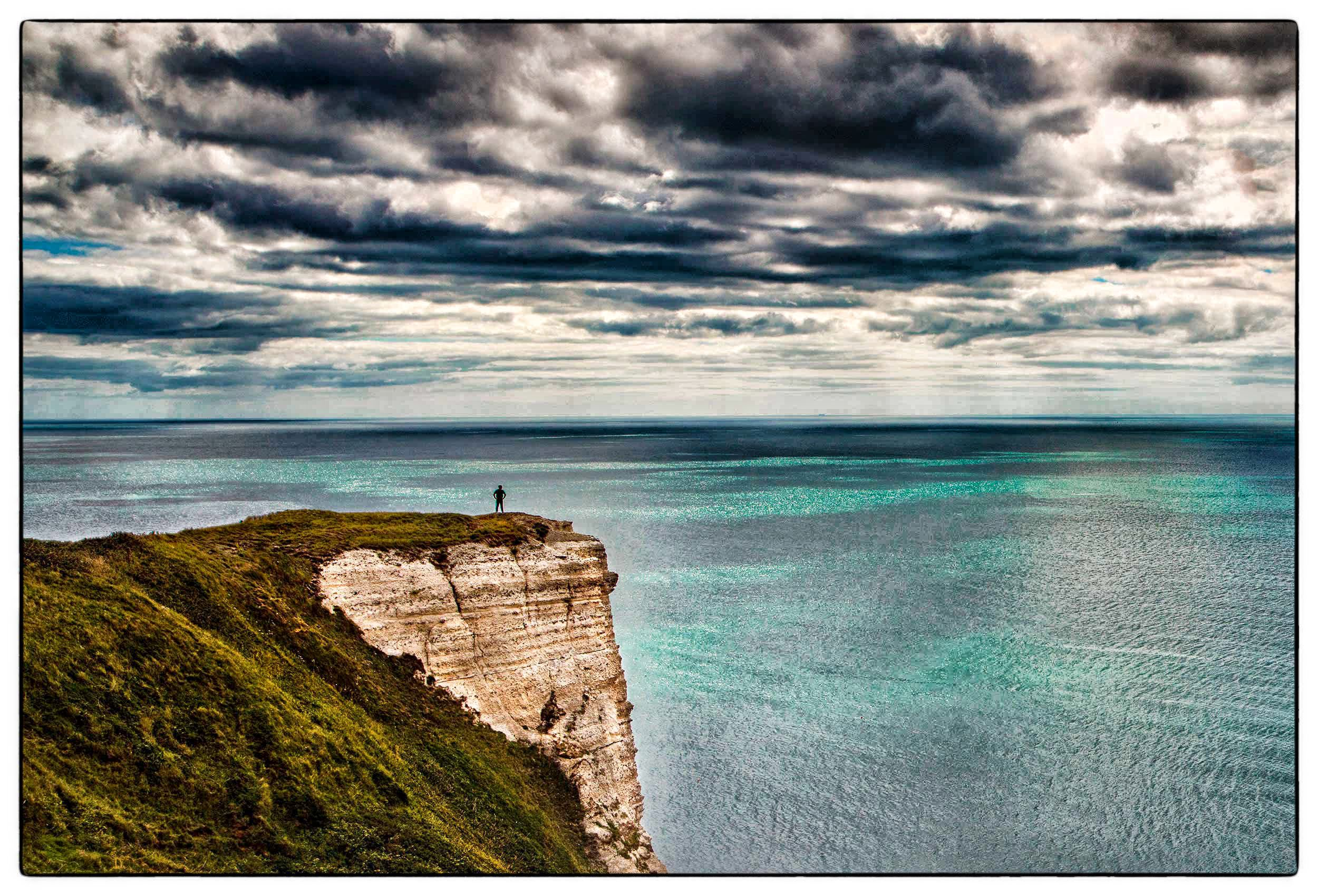 a-man-stands-on-a-cliff-near-lyme-regis-along-the-coastal-path-in-southwest-england