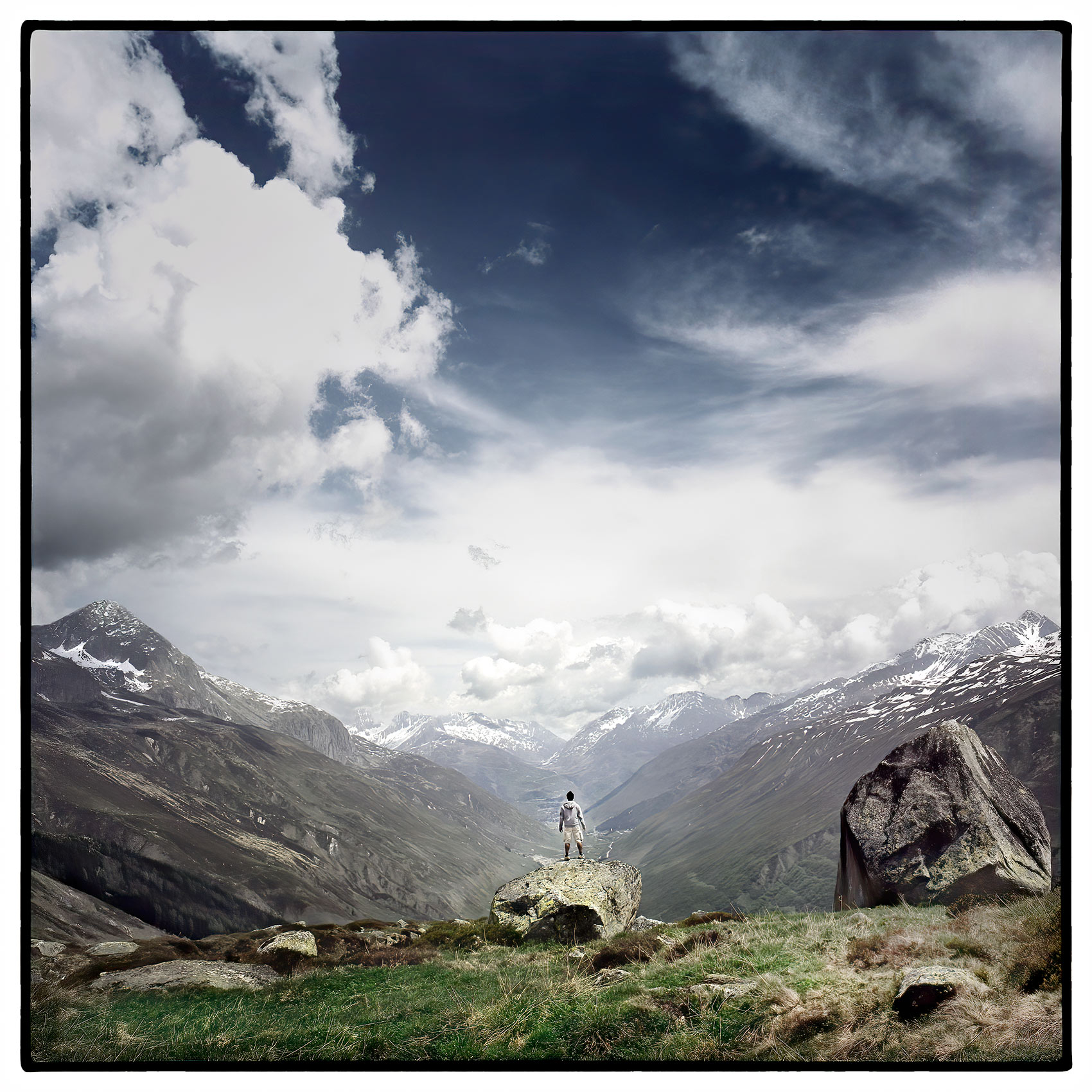 a-lone-man-stands-on-a-hillside-in-a-valley-looking-out-on-the-swiss-alps