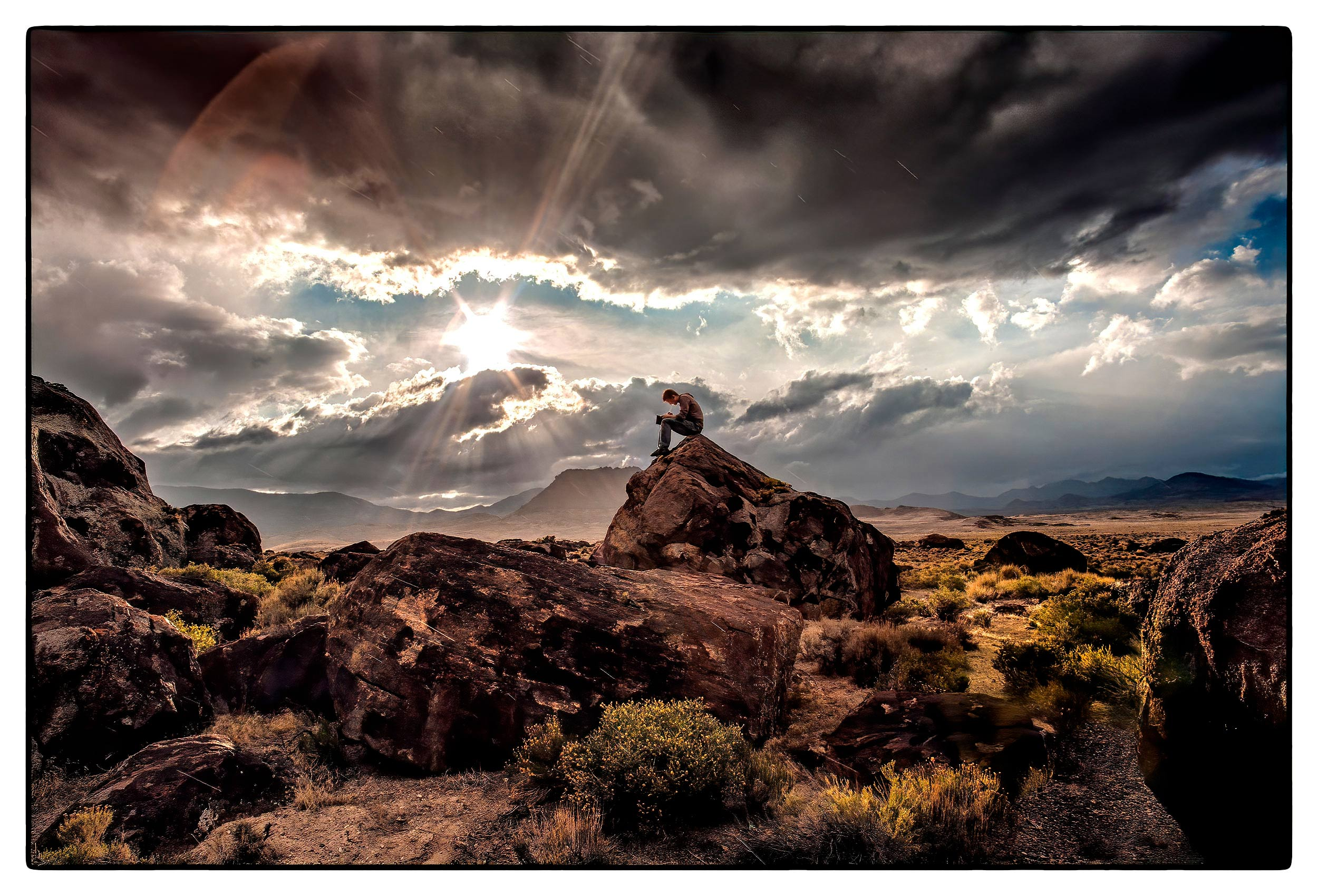 a-man-writes-in-his-journal-as-he-sits-on-a-rock-at-a-rest-stop-in-the-nevada-desert