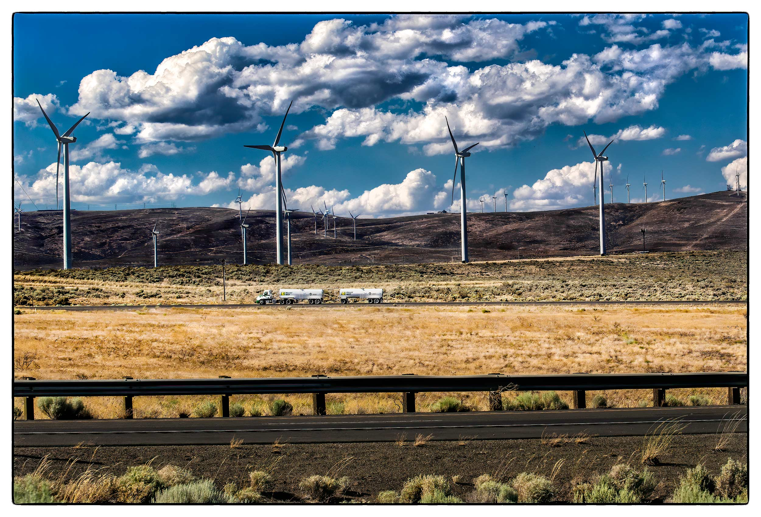a-millky-way-truck-drives-past-puget-sound-engerys-wind-turbine-farm-in-rural-kittitas-county-washington-state