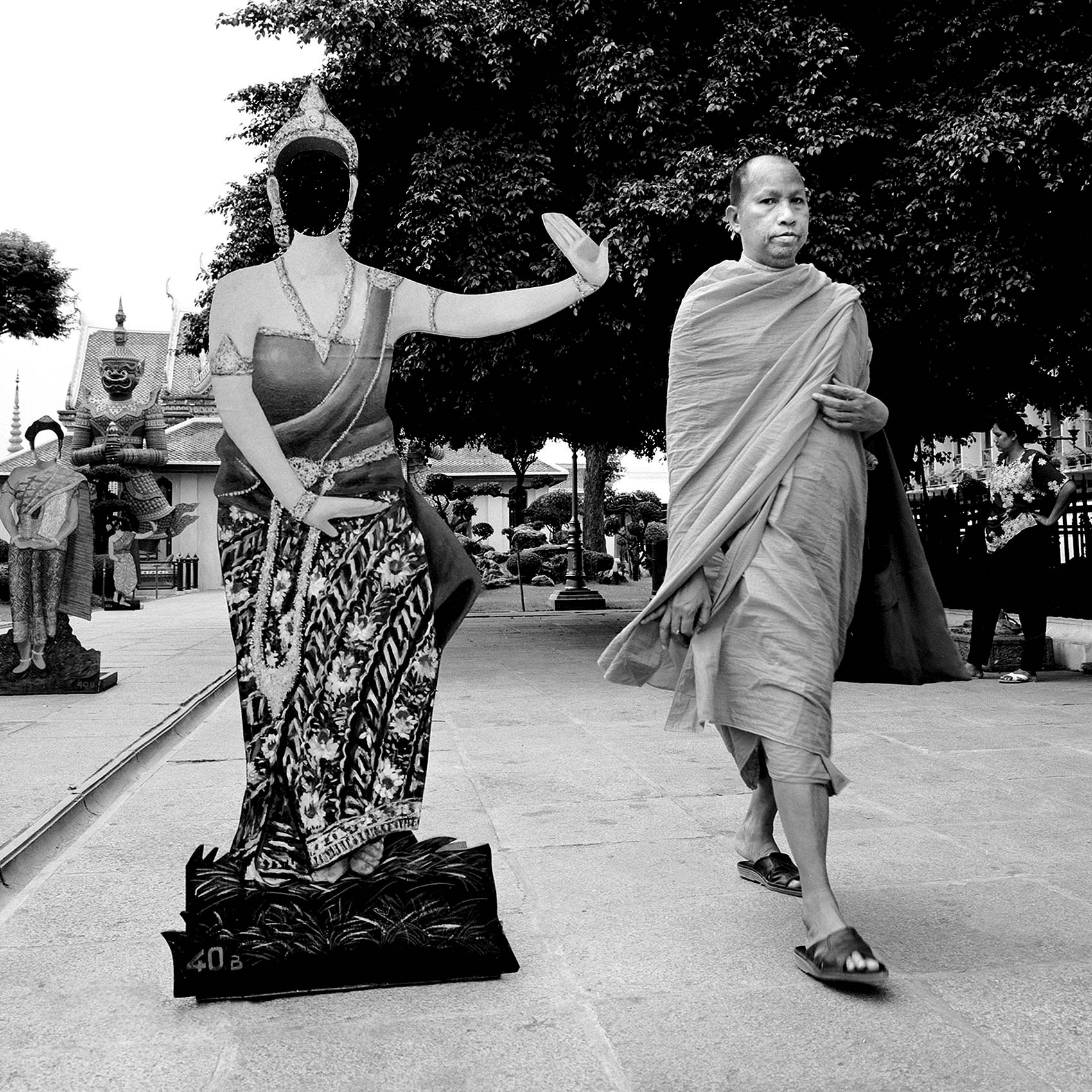 a-monk-walks-past-a-life-size-cut-out-of-a-thai-woman-in-traditional-dress-in-bangkok