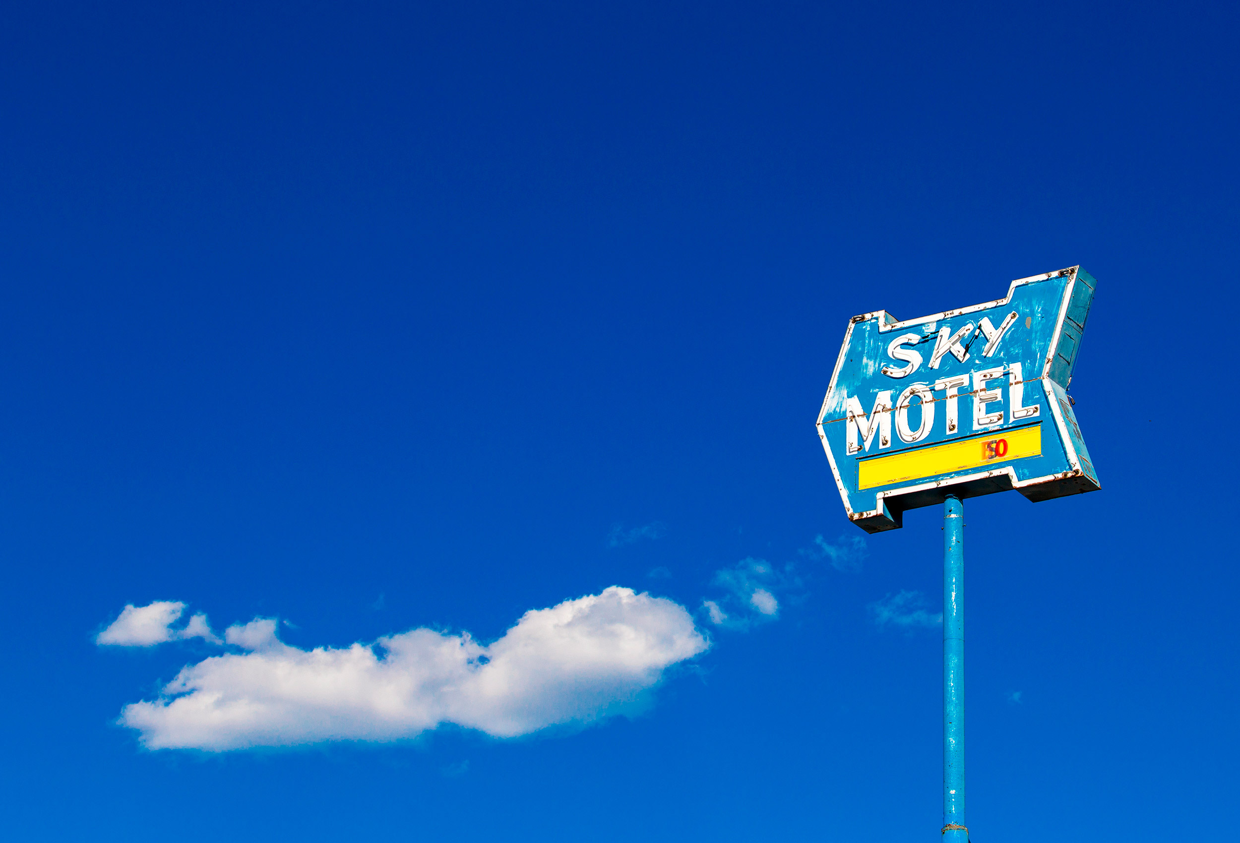 a motel sign against the deep blue sky by an award winning american travel photographer