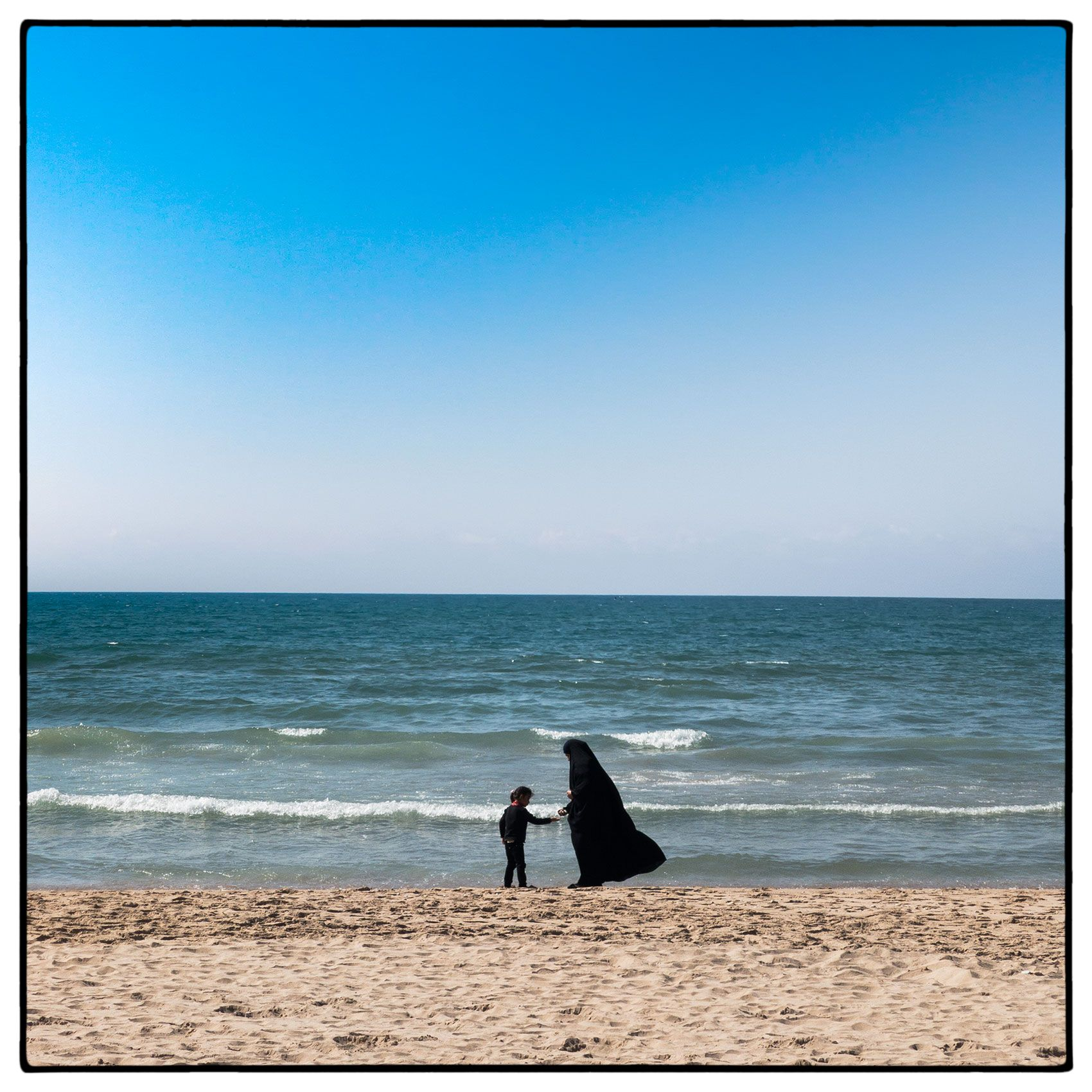 a-muslim-woman-in-a-burqa--with-her-daughter-on-the-beach-in-beirut-lebanon
