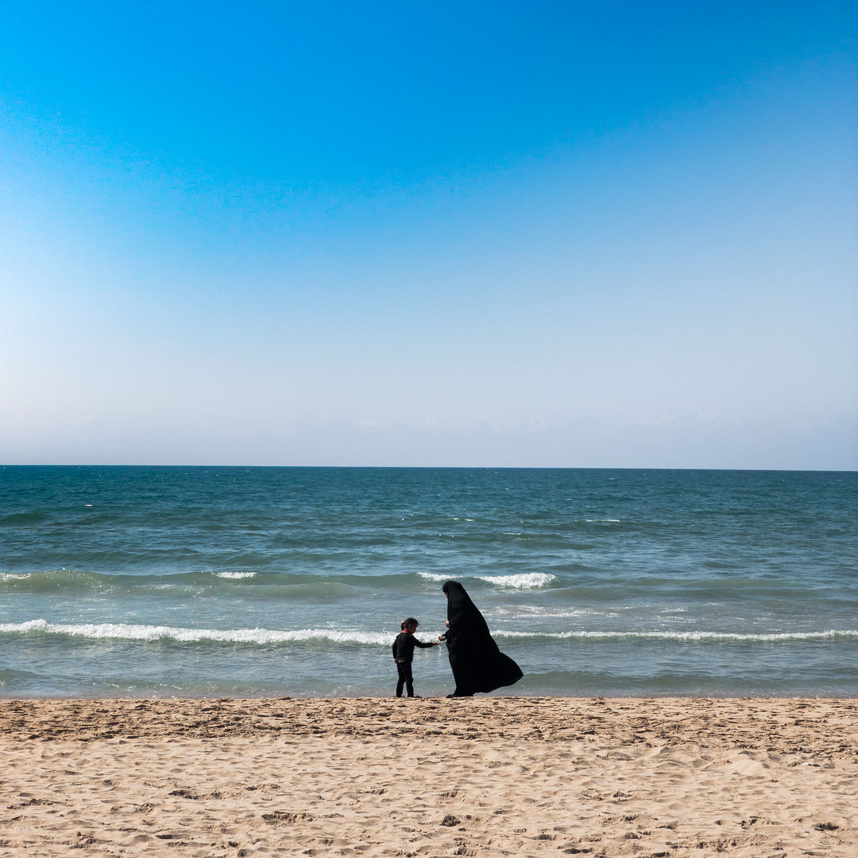 a muslim woman wears a burqua on a beach as she plays with her daughter in beirut