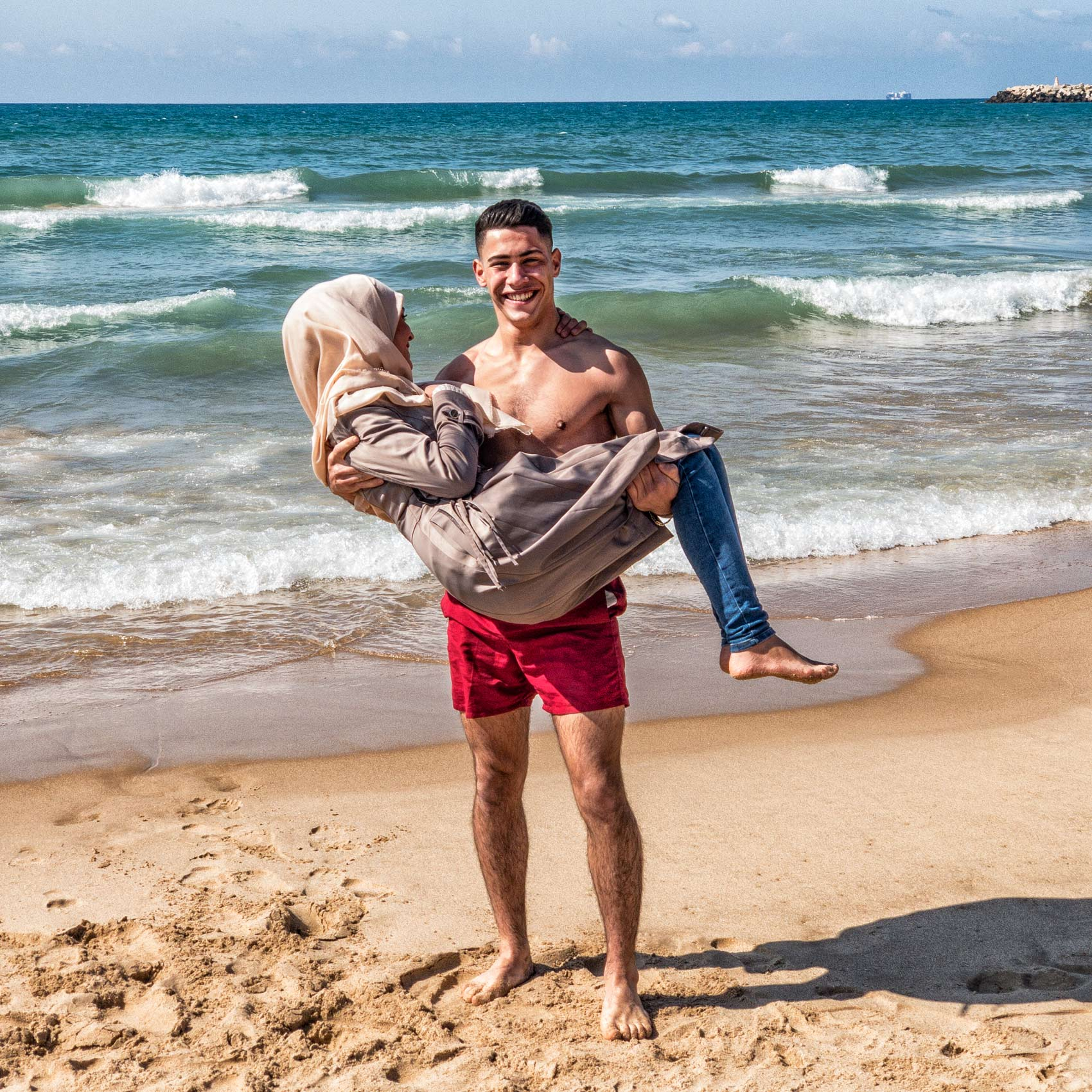 a lebanese man holds up his muslim girlfriend on a beach in beirut lebanon