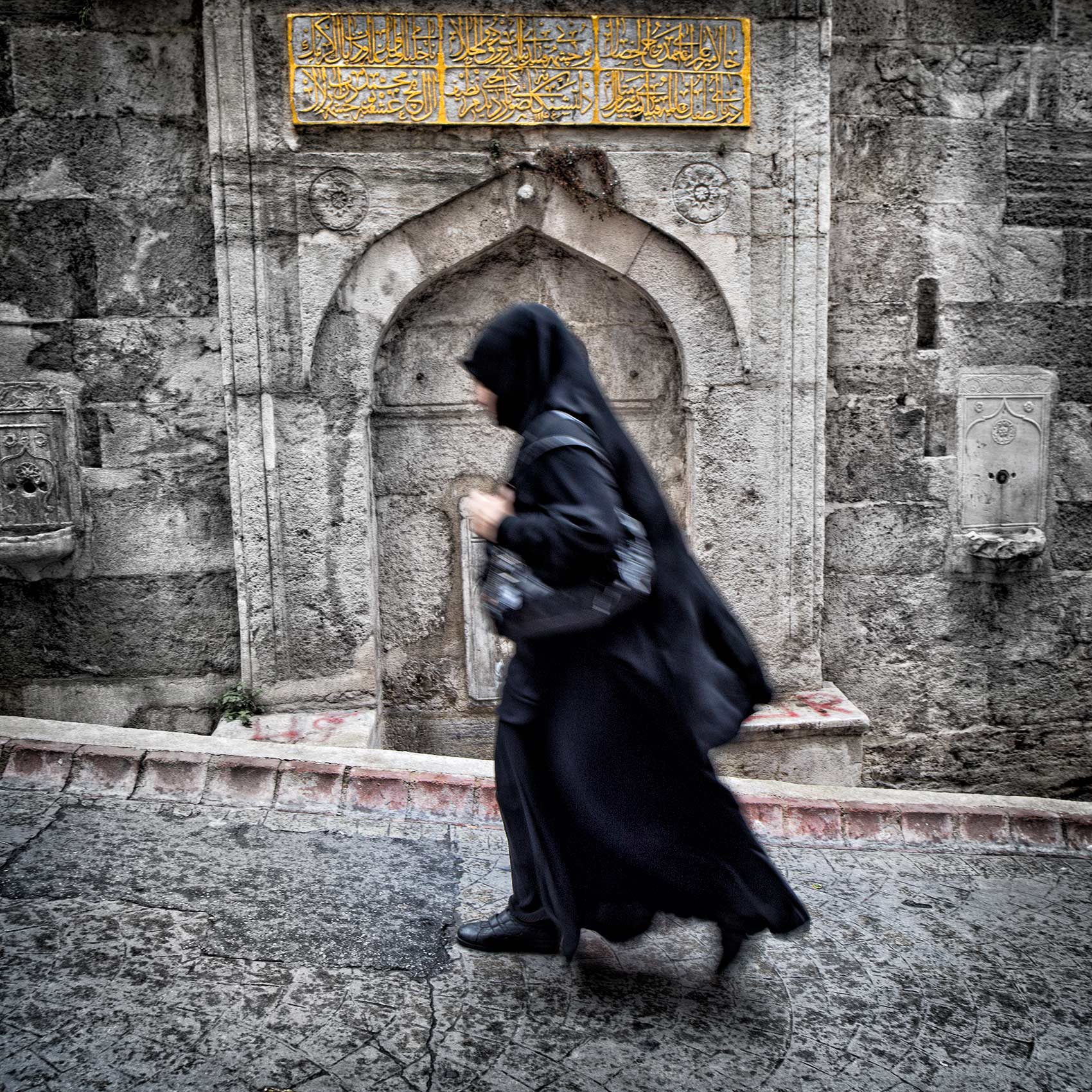 a-muslim-woman-walks-up-a-hill-in-the-beyoglu-district-of-istanbul