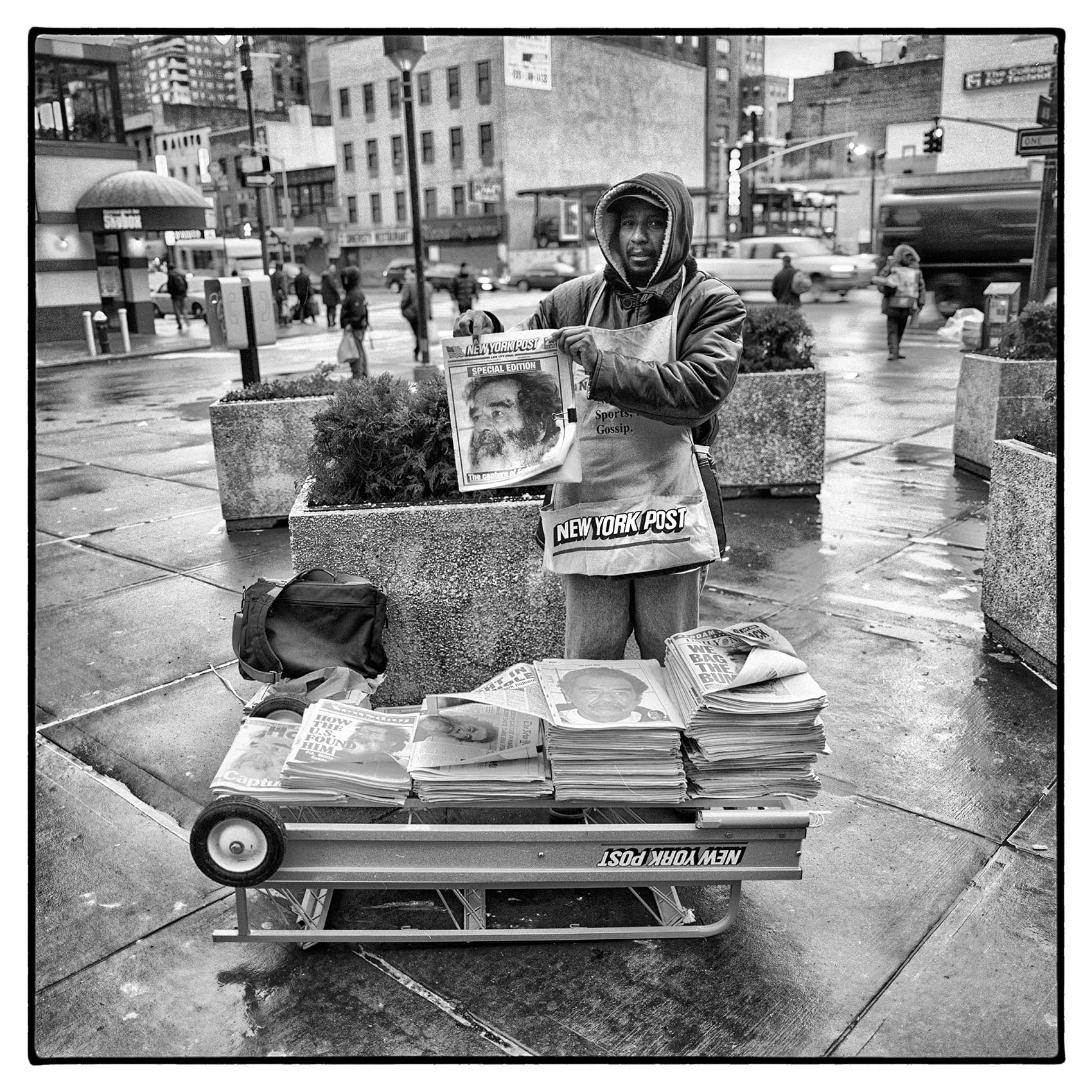 a-new-york-newspaper-vendor-holds-up-a-front-page-that-saddam-hussein-was-captured