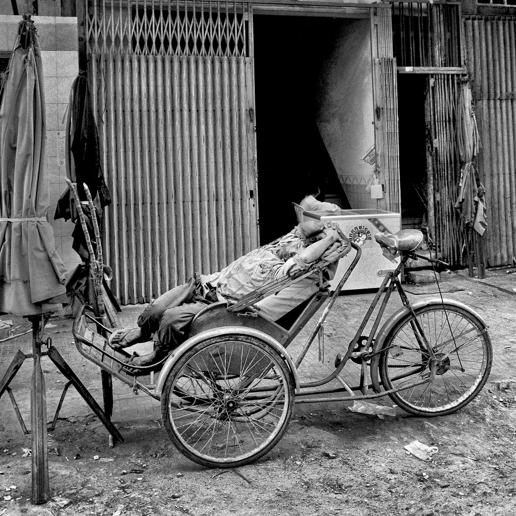 a-pedicab-driver-takes-a-nap-while-on-a-break-on-the-streets-of-phnom-penh-cambodia