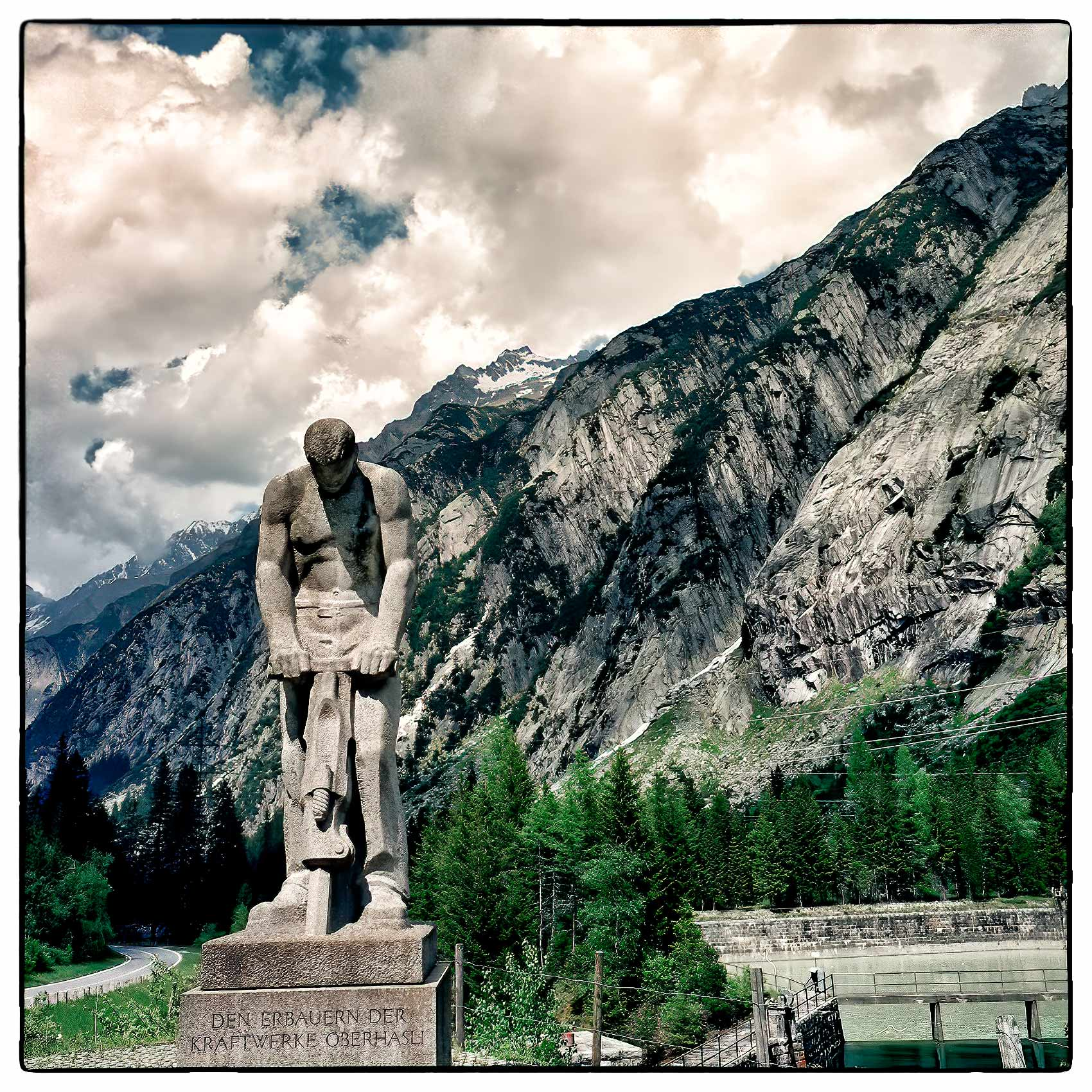 a-statue-of-a-construction-worker-stands-near-an-automobile-tunnel-in-the-swiss-alps