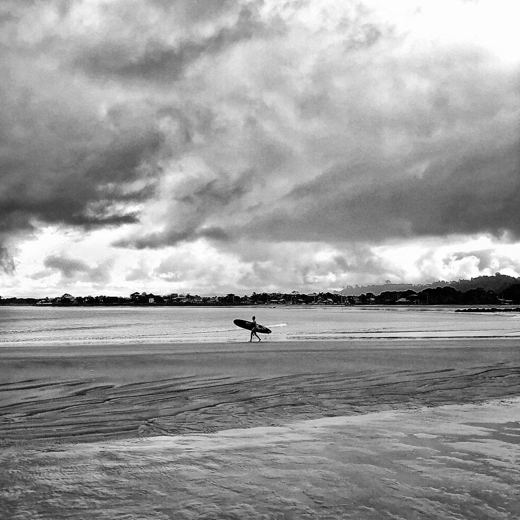 a-surfer-walking-on-the-beach-in-mompiche-ecuador-in-the-early-morning